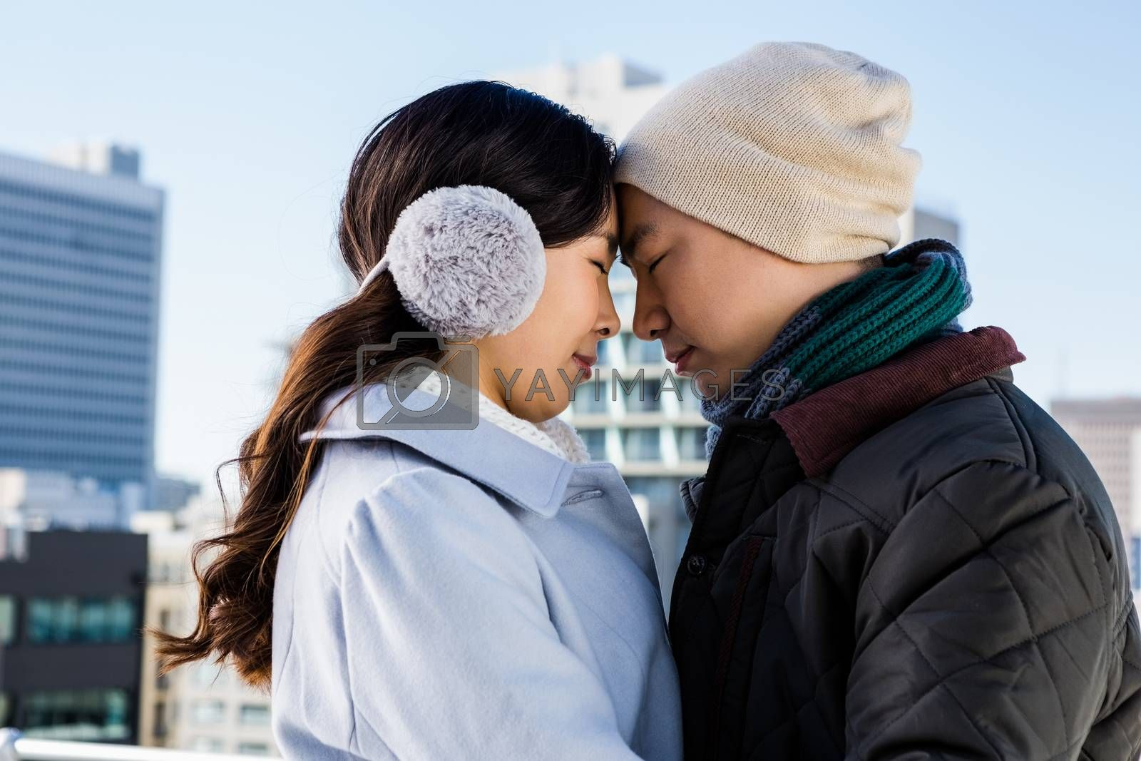 Affectionate couple in warm clothing head to head