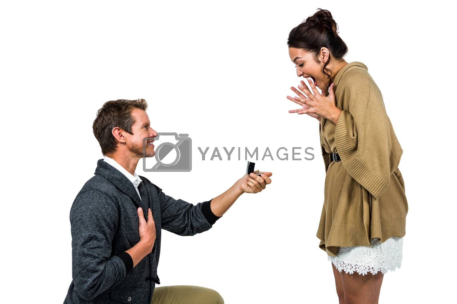 Happy man offering engagement ring to partner against white background