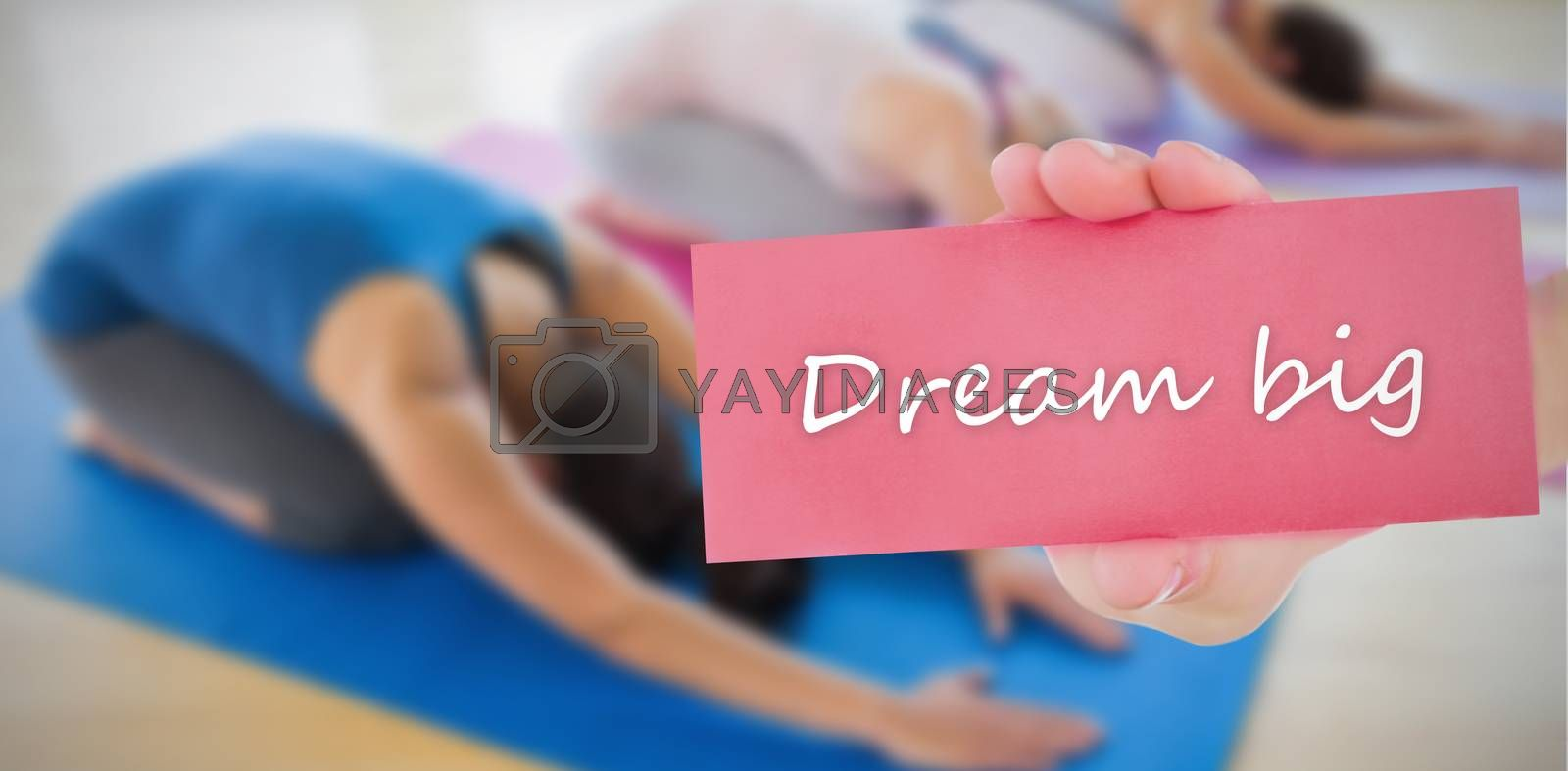 The word dream big and hand showing card against