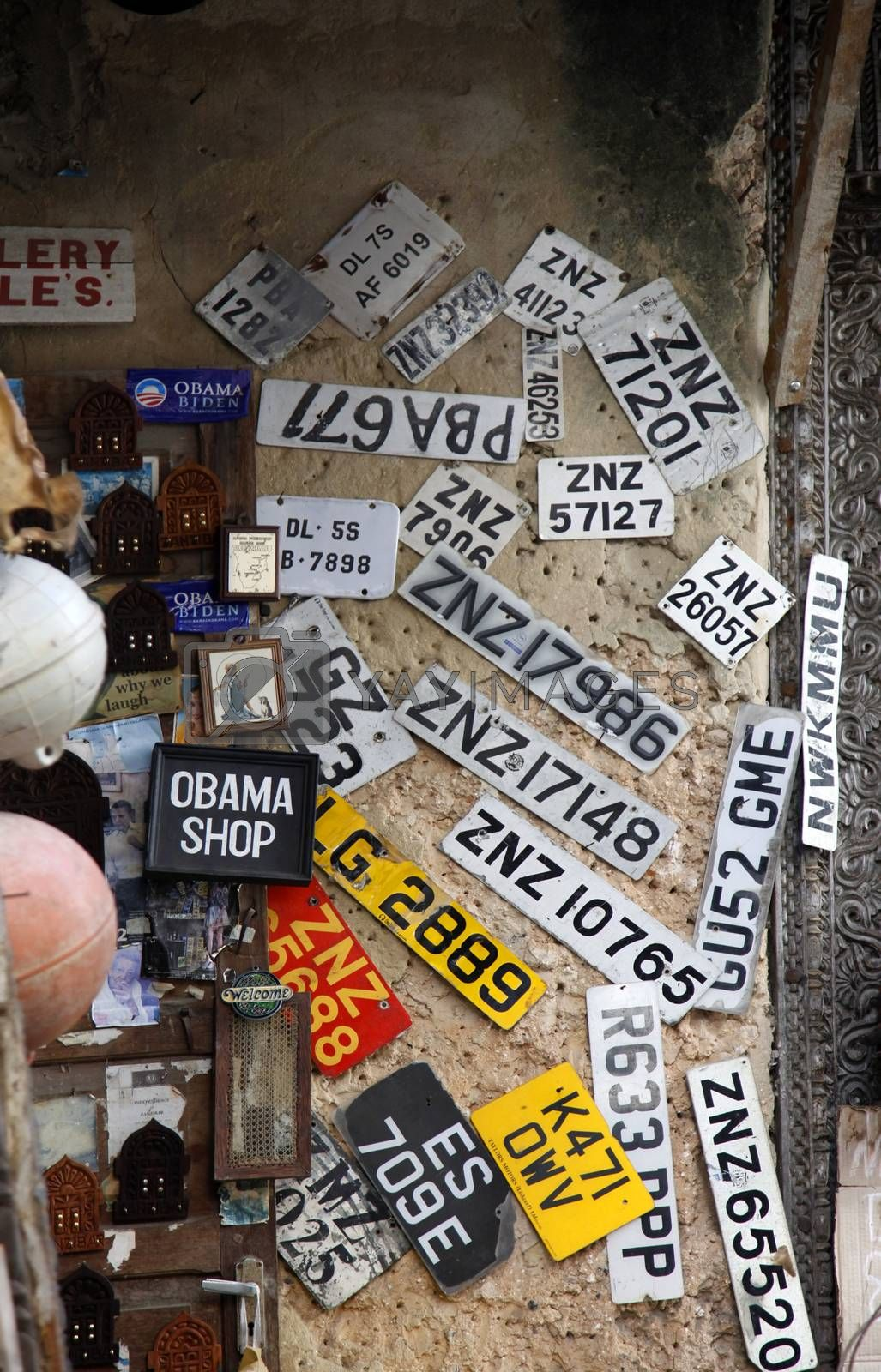 Stone town, Tanzania - December 30, 2015: Stone Town. Streets of the town are always lively. There are many shops, restaurants and bars, where tourists can relax and buy suvenirs. Here is a man apparently collecting old number plates.