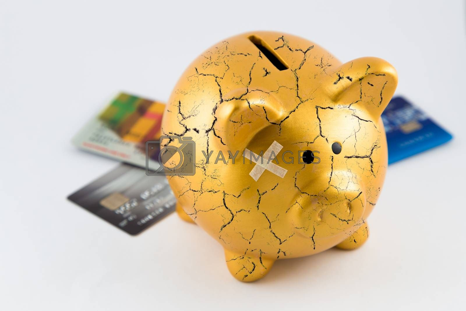 Right side of gold piggy bank cracked with plaster and blurred credit cards on isolated white background