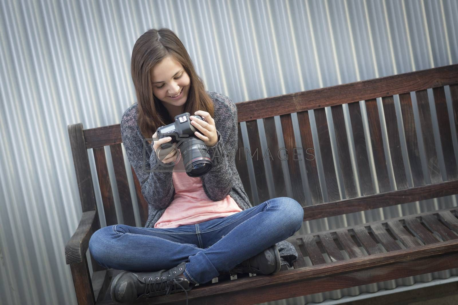 Royalty free image of Young Girl Photographer Looking at Back of Camera by Feverpitched
