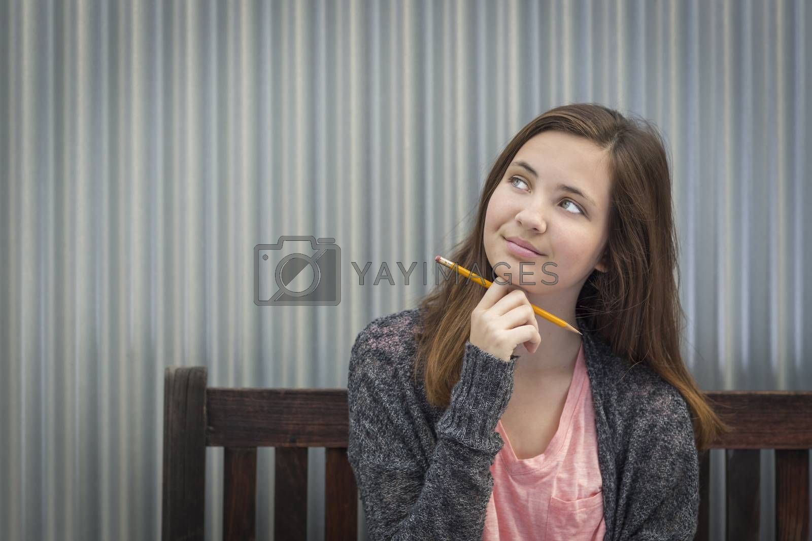 Royalty free image of Young Daydreaming Female Student With Pencil Looking to the Side by Feverpitched
