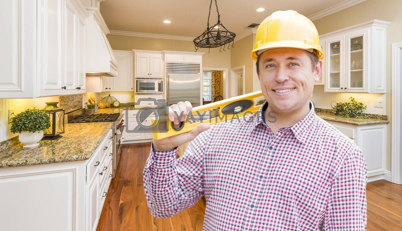 Royalty free image of Contractor with Level Wearing Hard Hat Standing In Custom Kitche by Feverpitched