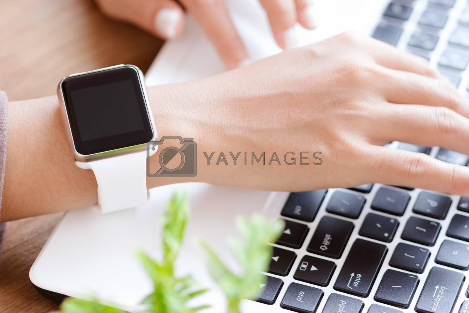 closeup hand watch using laptop on desk