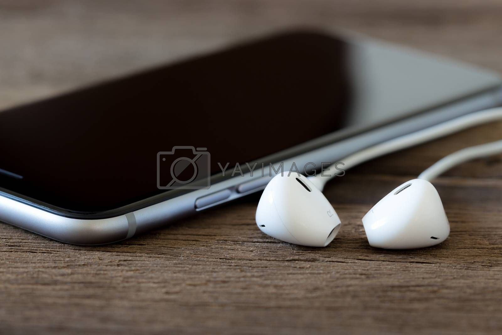 Royalty free image of closeup phone and earbud on wood desk by blackzheep