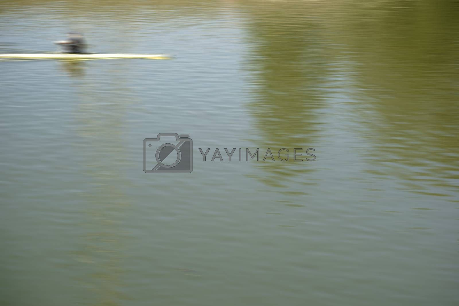 A blurred sports rowing boat cuts through a abstract water surface.