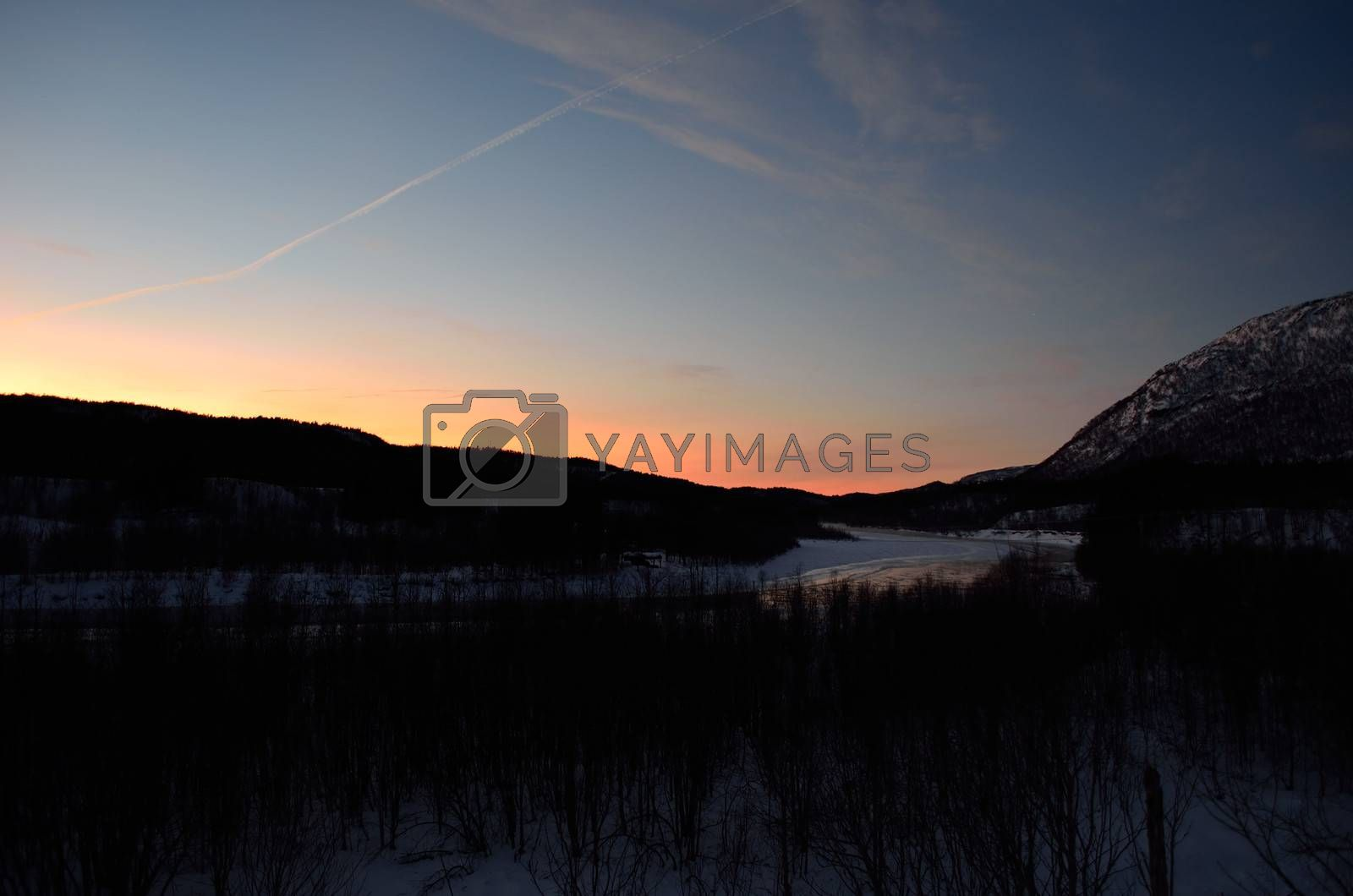 Royalty free image of vibrant sunset sky over mountain forest and icy river in winter by Finephotoworks