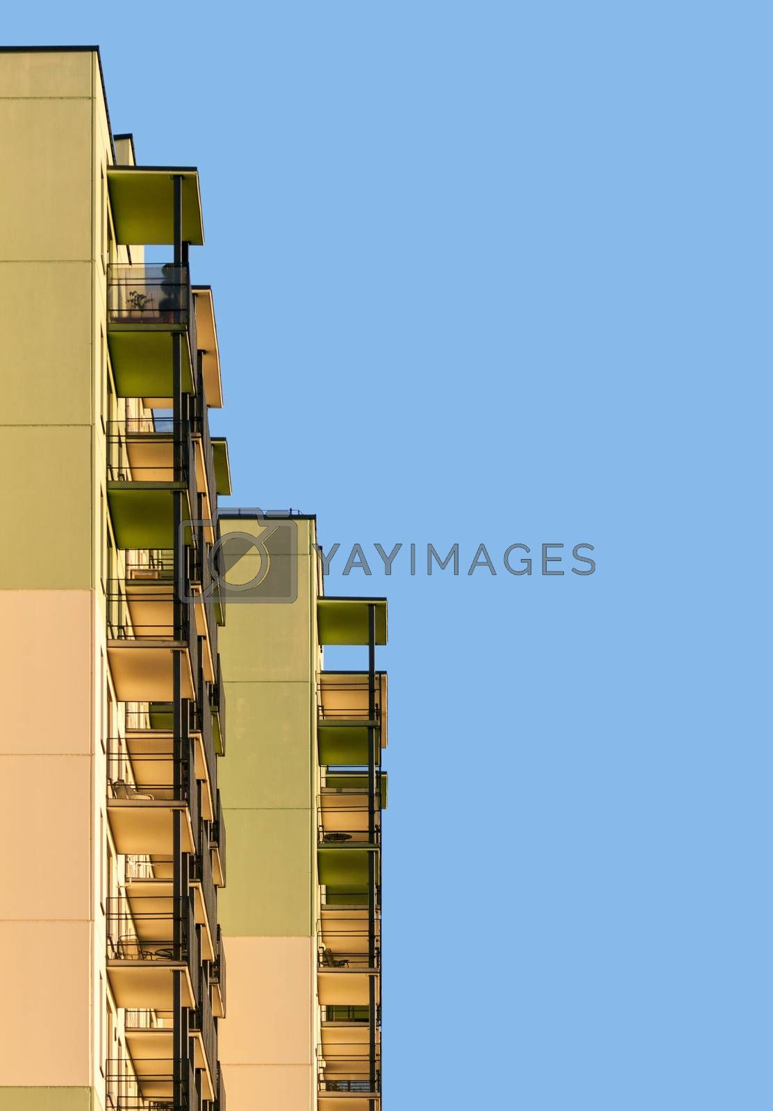 Abstract picture of modern apartment building with balconies against blue sky