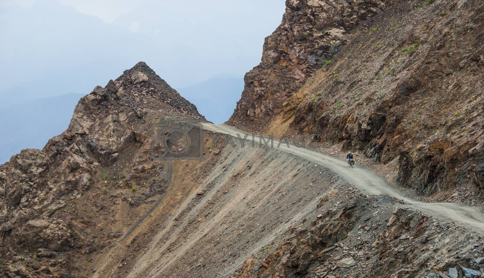 Royalty free image of Bicycle tourist on the mountain road by shkonst