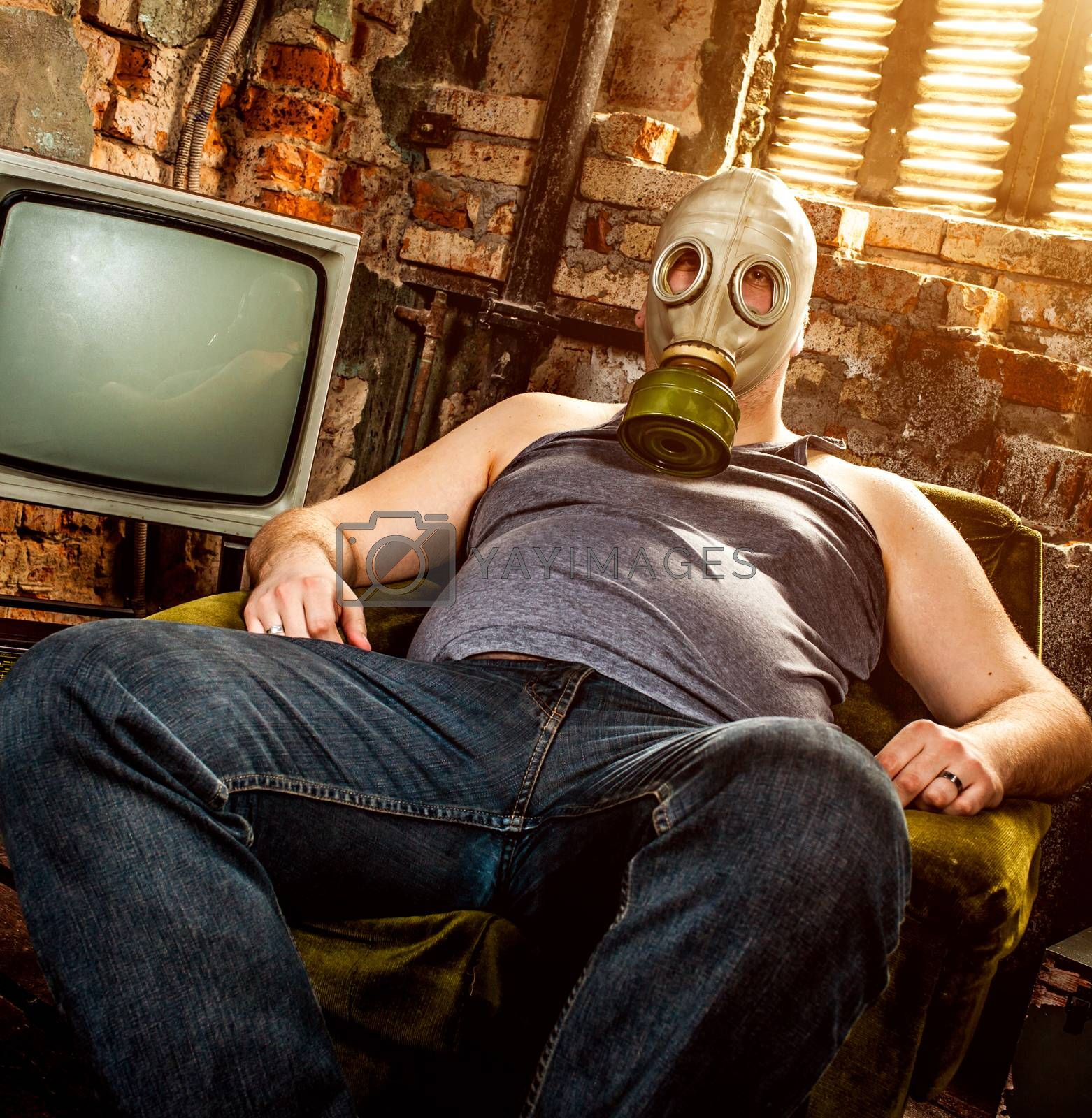 person in a gas mask sits on an armchair