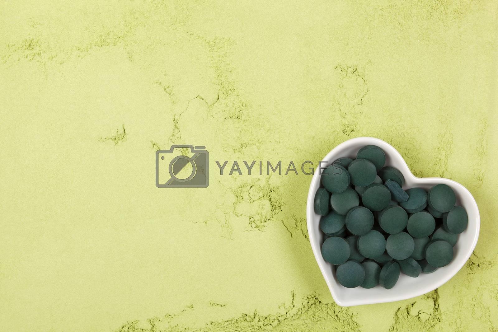 Spirulina; chlorella and wheatgrass. Green food supplement. Green pills and ground powder. Healthy lifestyle.