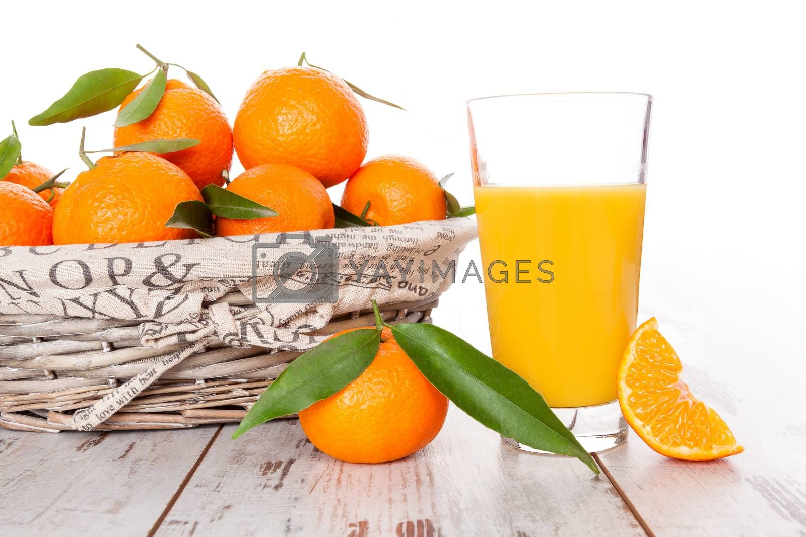 Mandarine fruit and juice in white wooden basket on white wooden table. Provence style.
