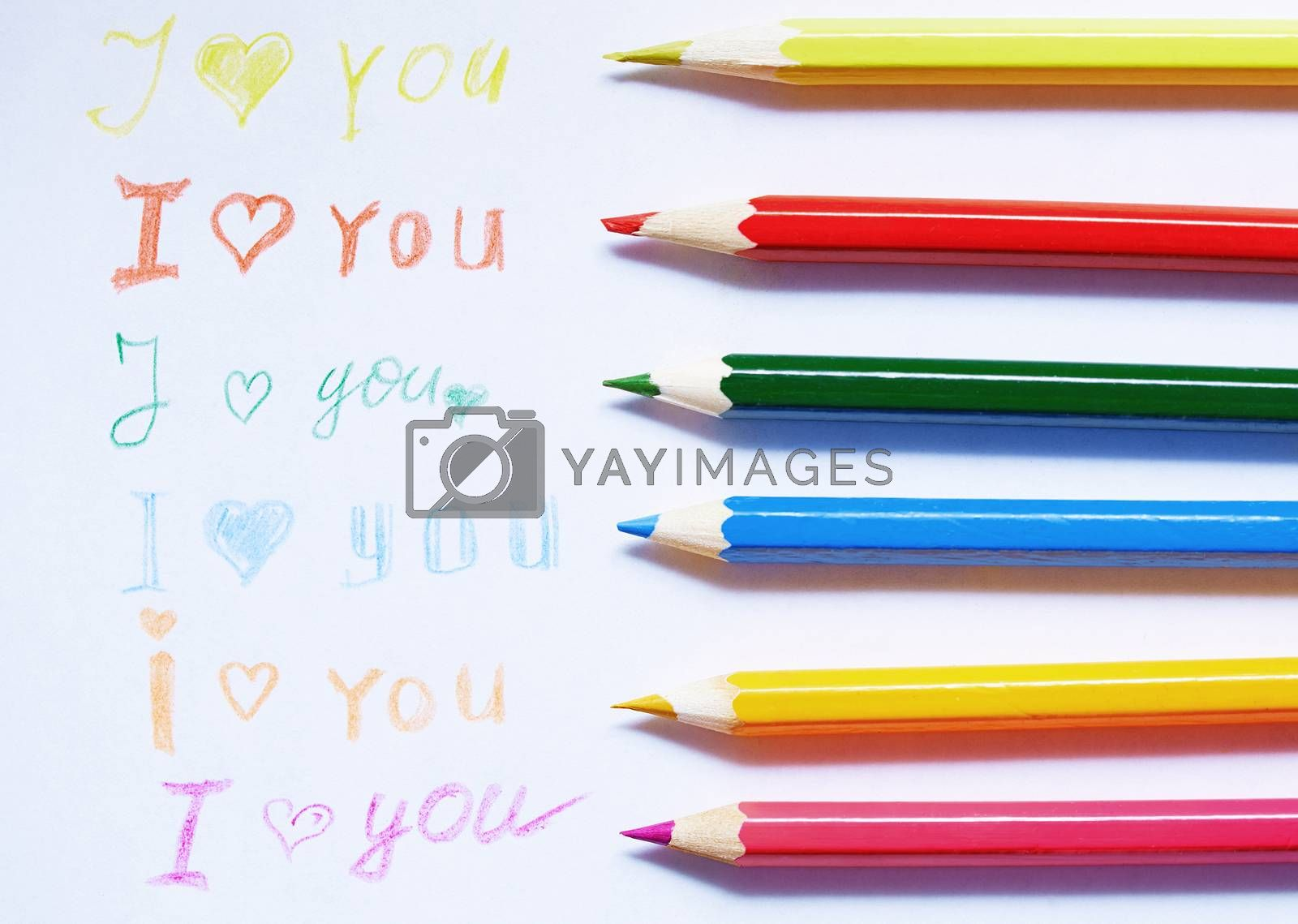 Paper with love you message and colored pencils