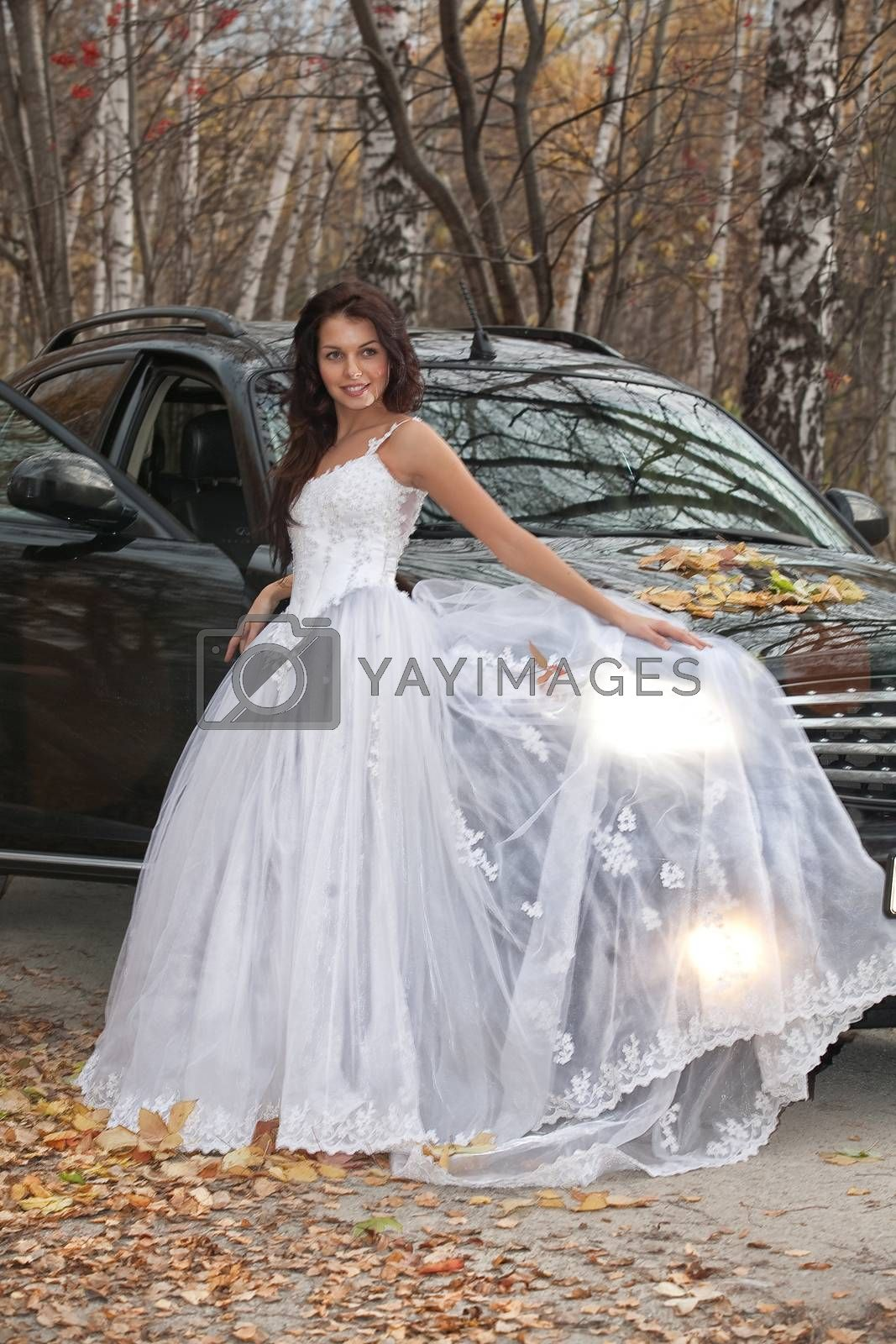 Young woman in a wedding dress standing near the jeep in an autumn forest