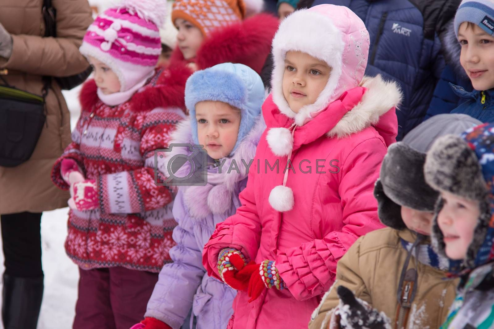 Volgograd, Russia - January 7, 2016: Two girls stand in a crowd of children on a small childrens New Years celebration in the playground in the yard
