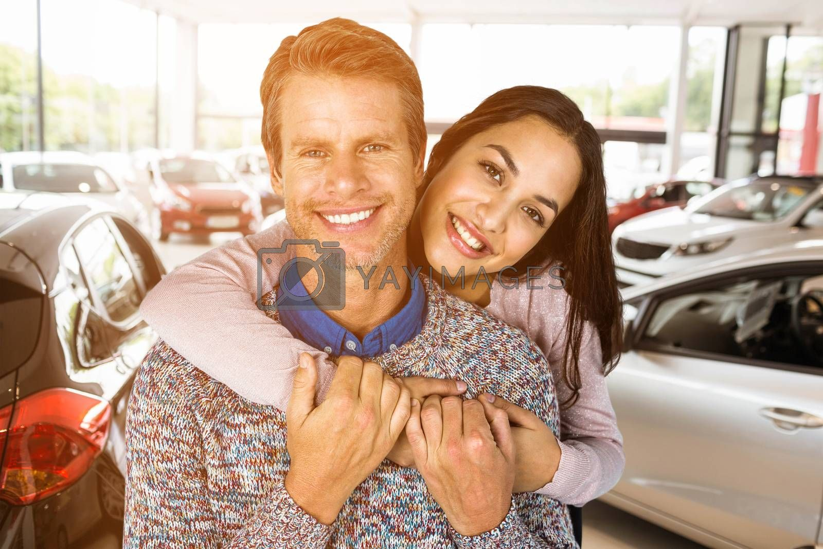 Close-up of happy couple against view of row new car