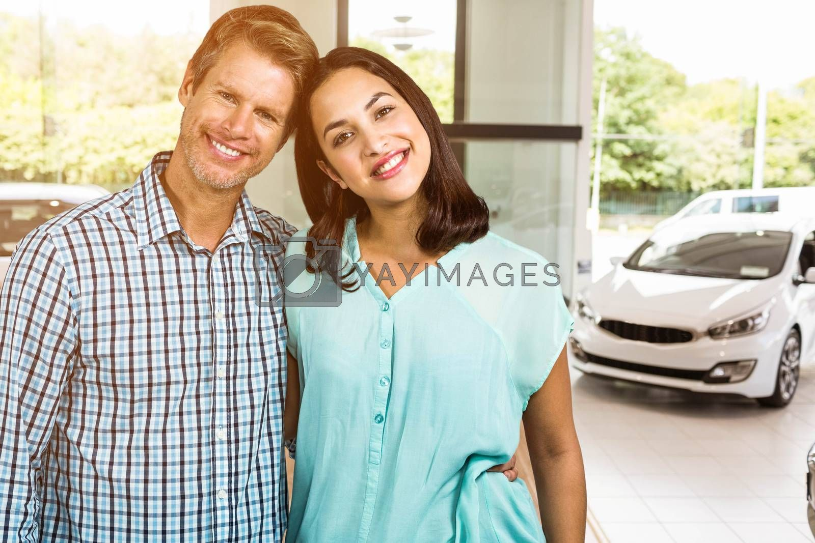 Portrait of happy couple standing against view of row new car