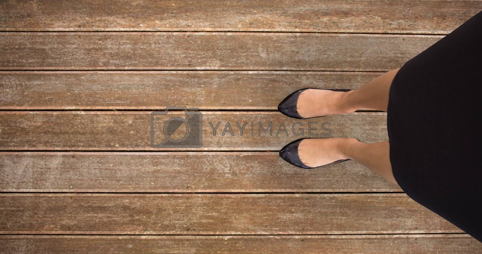 Businesswomans feet against wooden planks background