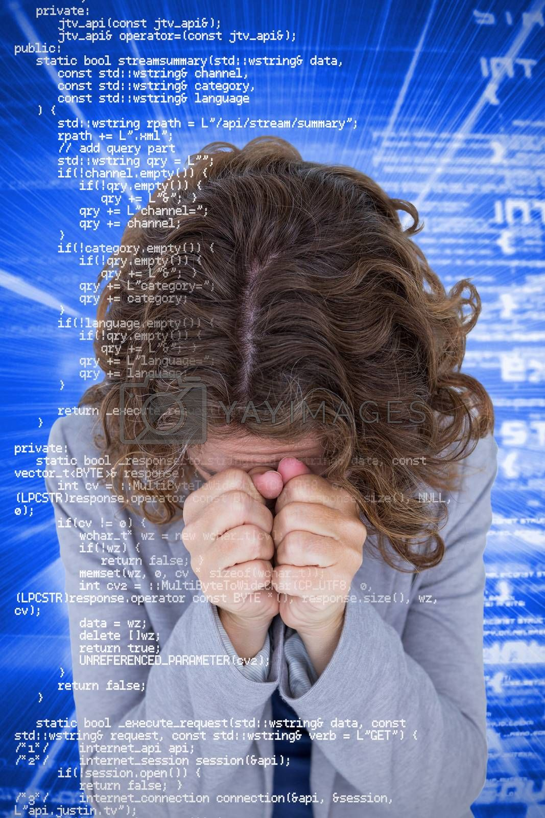 Upset woman with hands covering face against blue background with coding