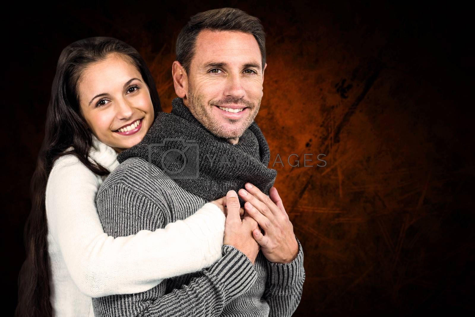 Smiling couple hugging and looking at camera against shades of brown