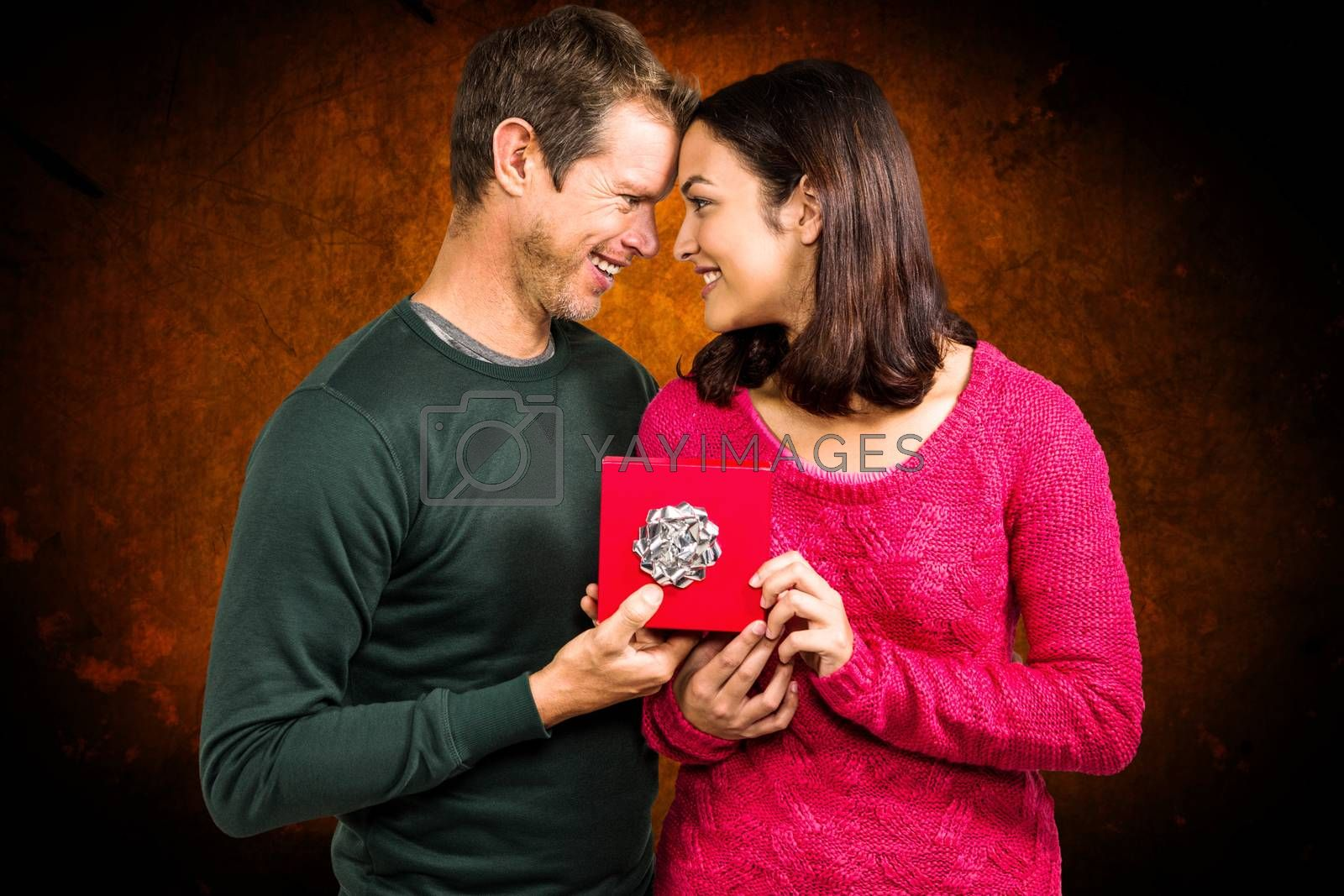 Happy couple holding gift box  against shades of brown