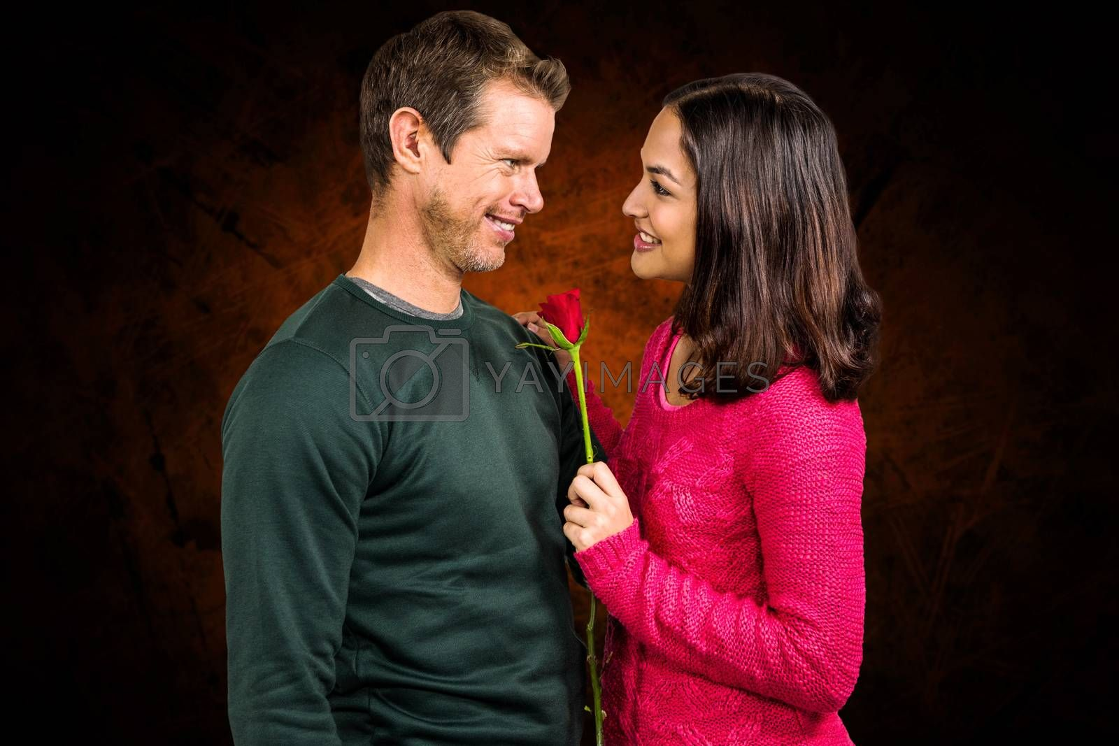 Smiling couple with red rose  against shades of brown
