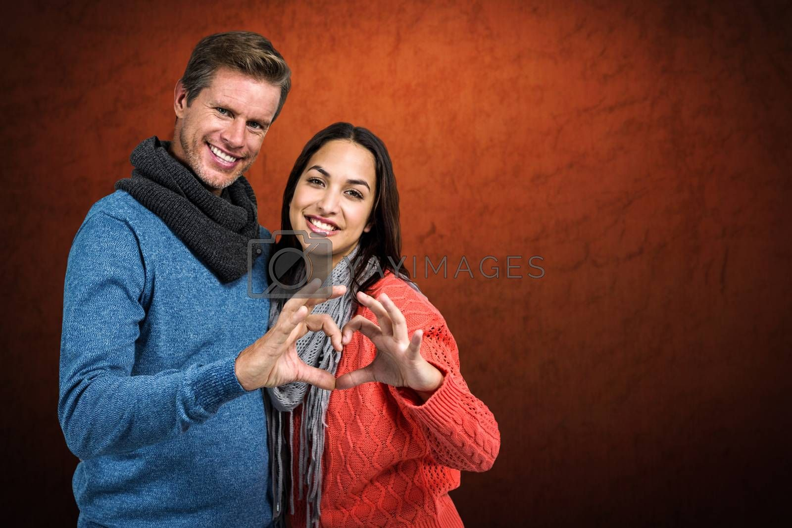 Portrait of couple making heart shape with hands against shades of brown