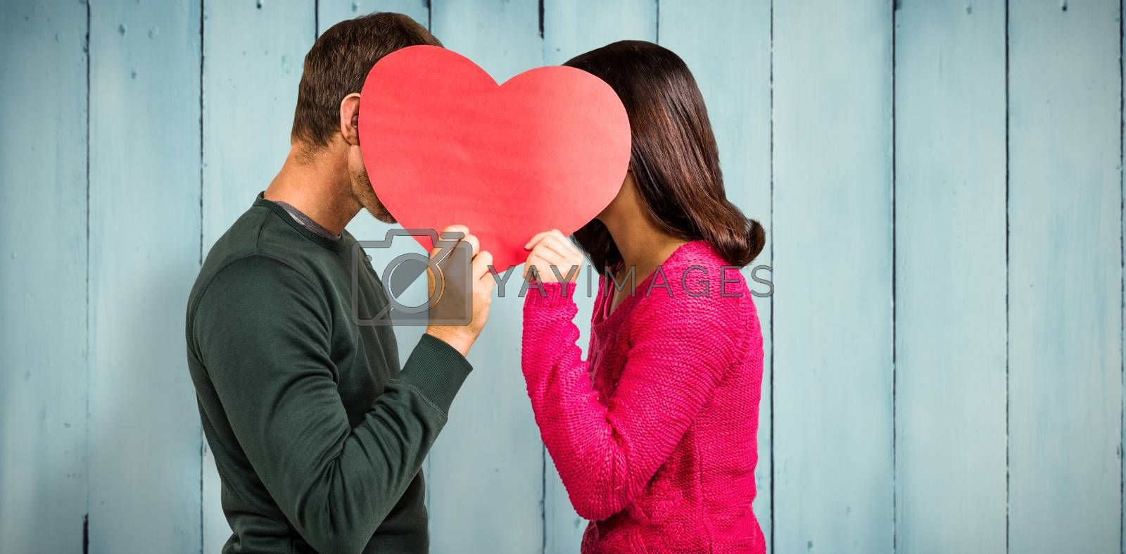 Couple covering faces with heart shape  against wooden planks