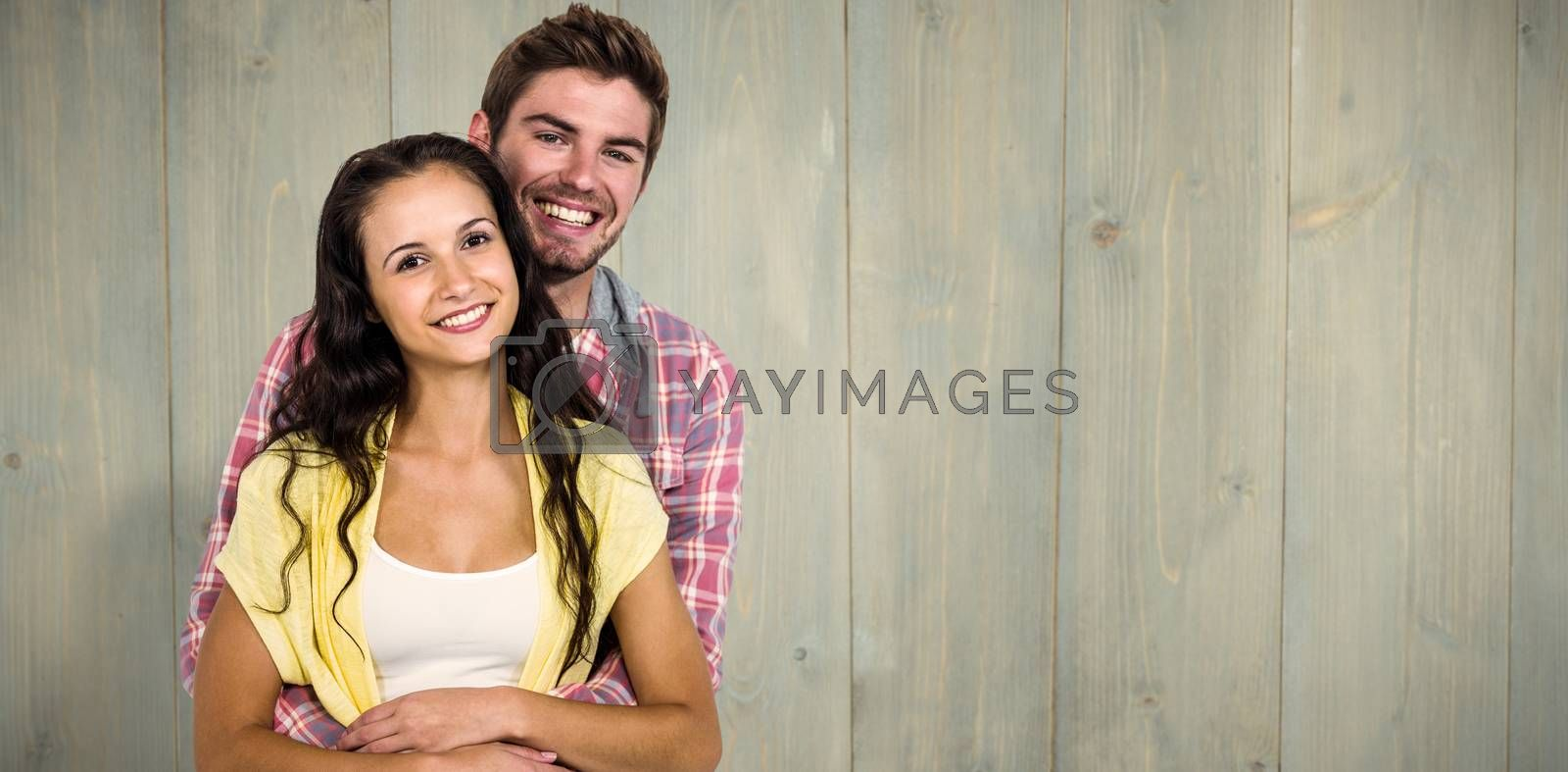 Happy couple hugging and looking at camera against wooden planks