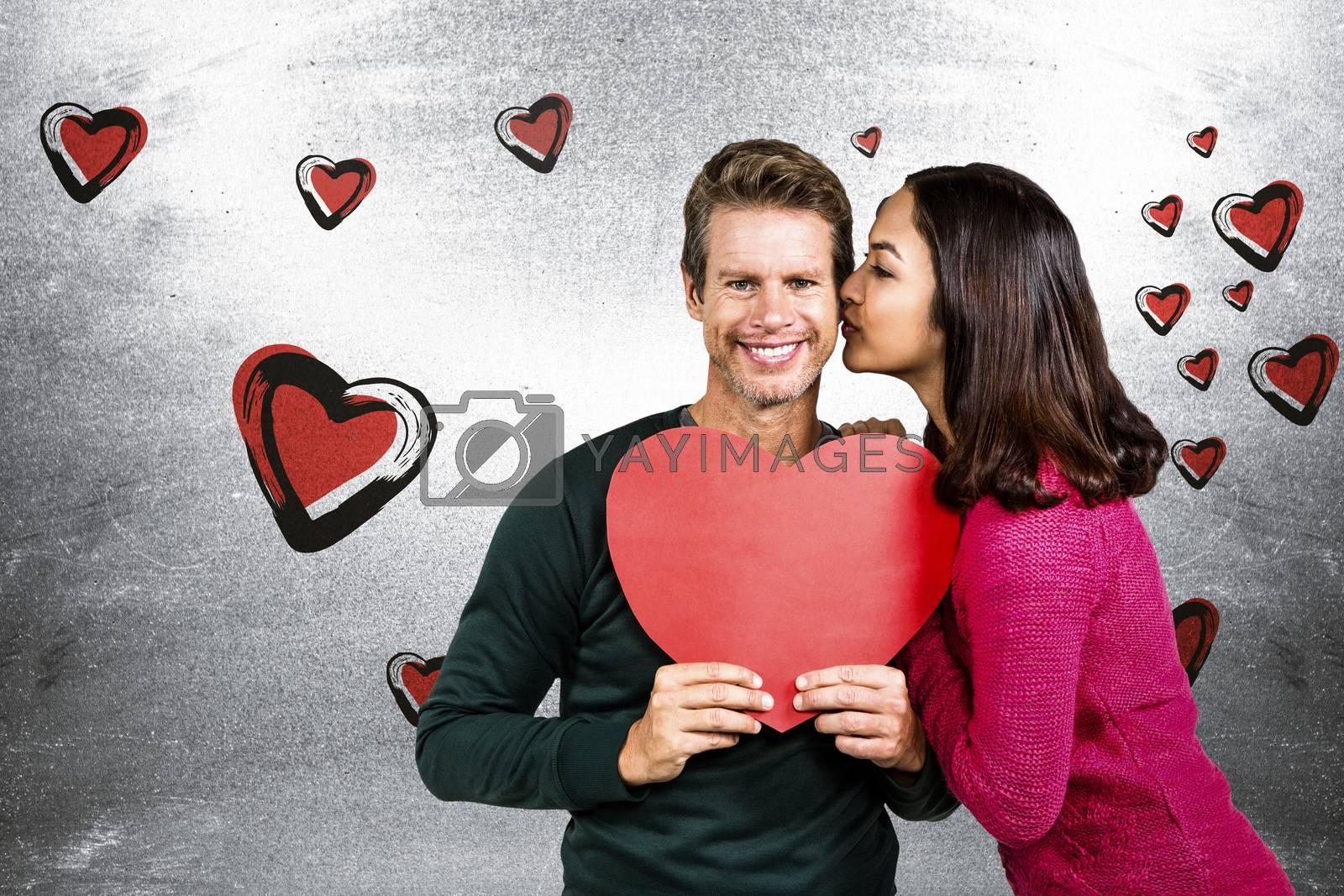 Woman kissing boyfriend with red heart shape  against blackboard