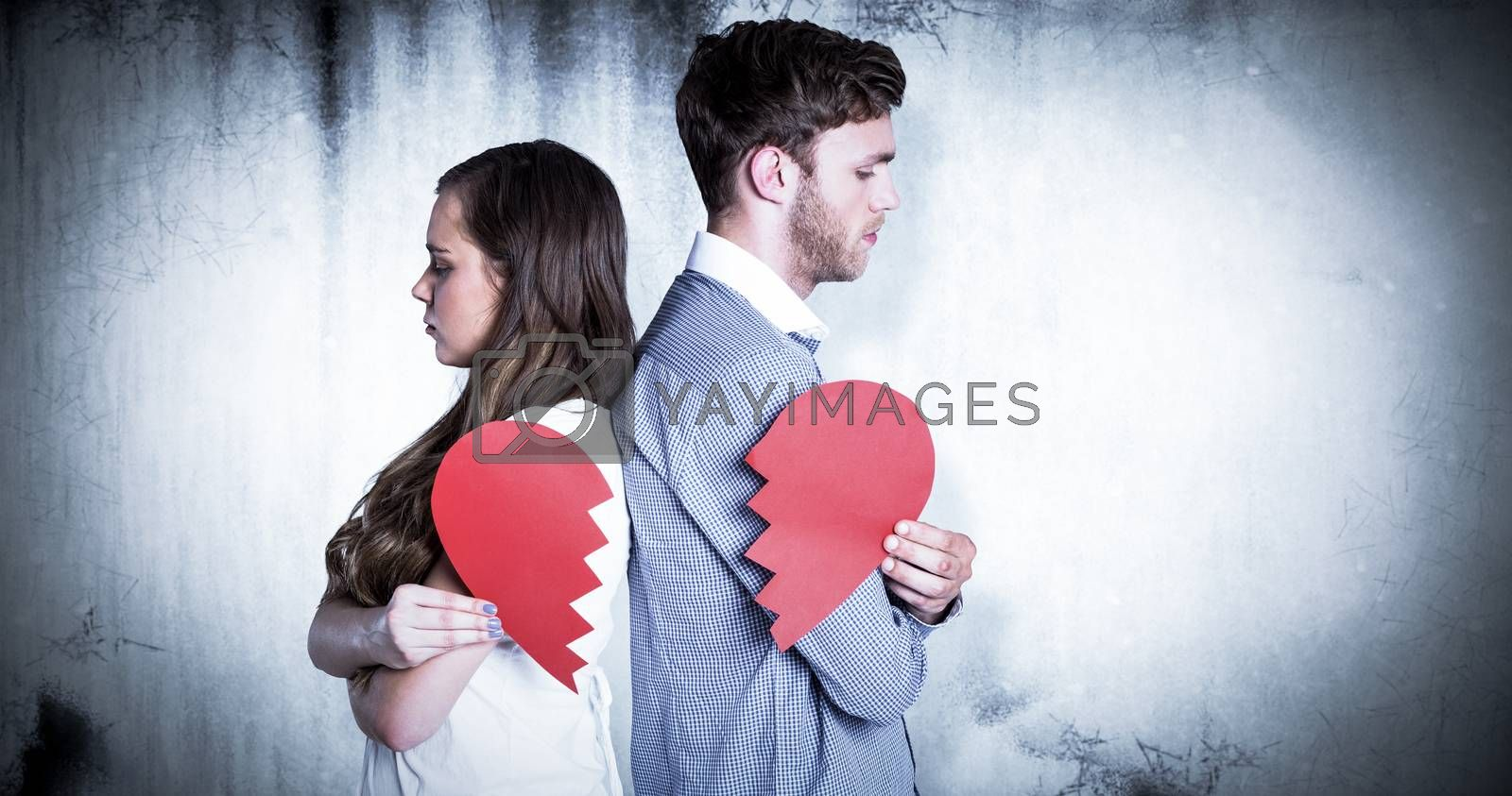 Side view of young couple holding broken heart against grey background