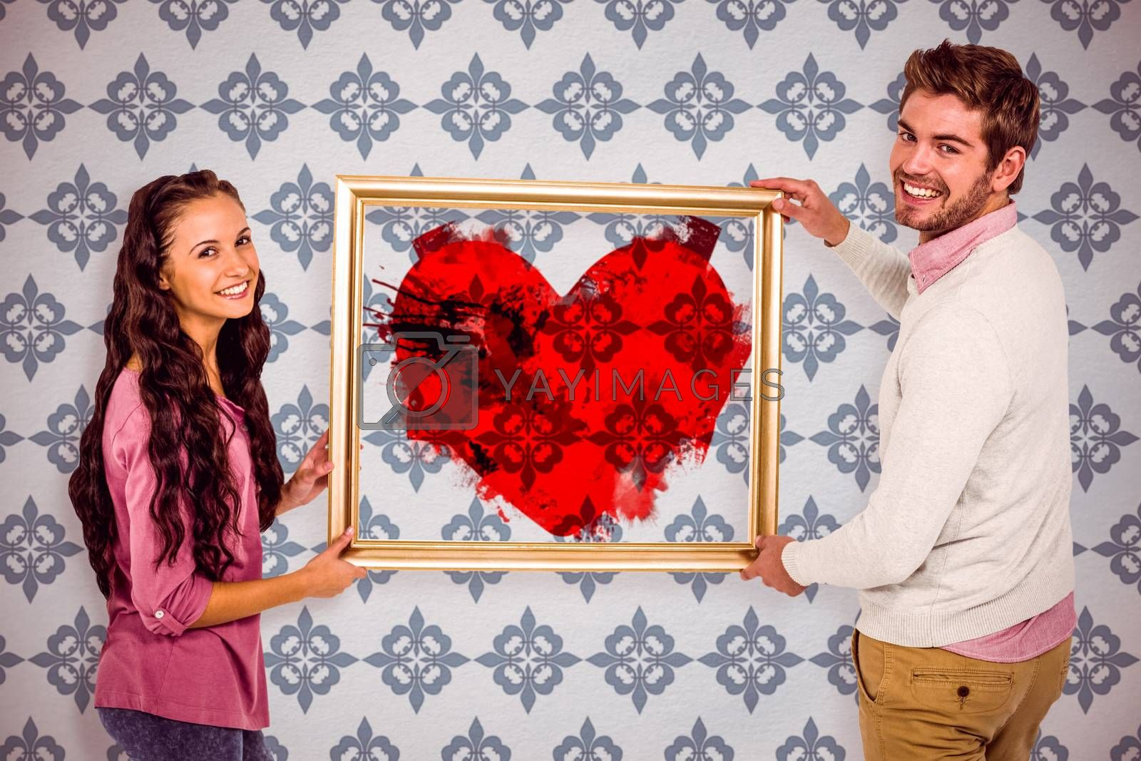 Smiling couple holding picture frame against blue background
