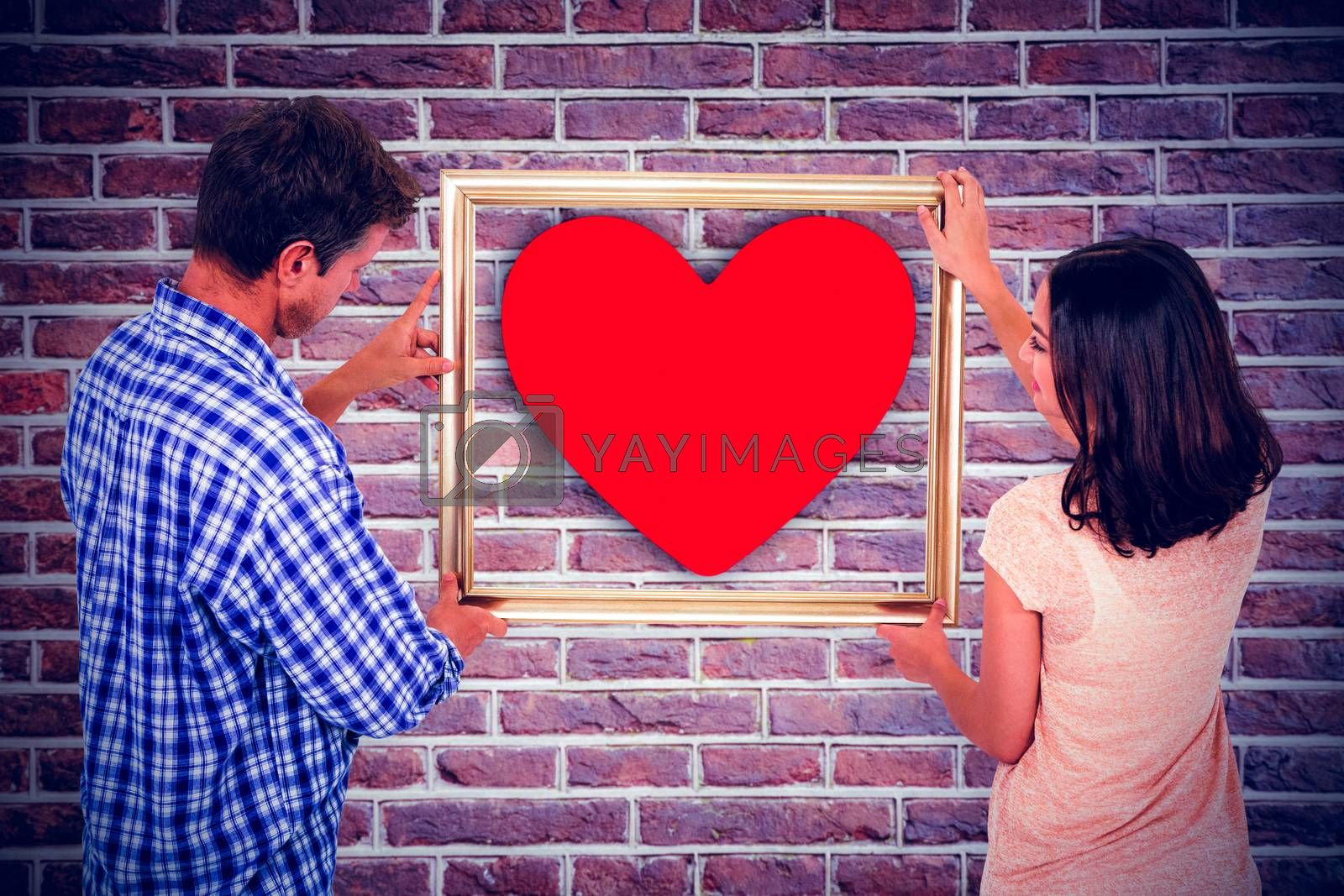 Composite image of couple holding picture frame by Wavebreakmedia
