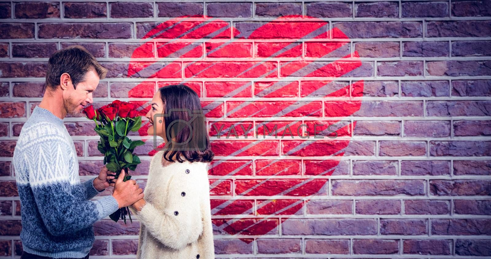 Romantic couple holding red roses against red brick wall
