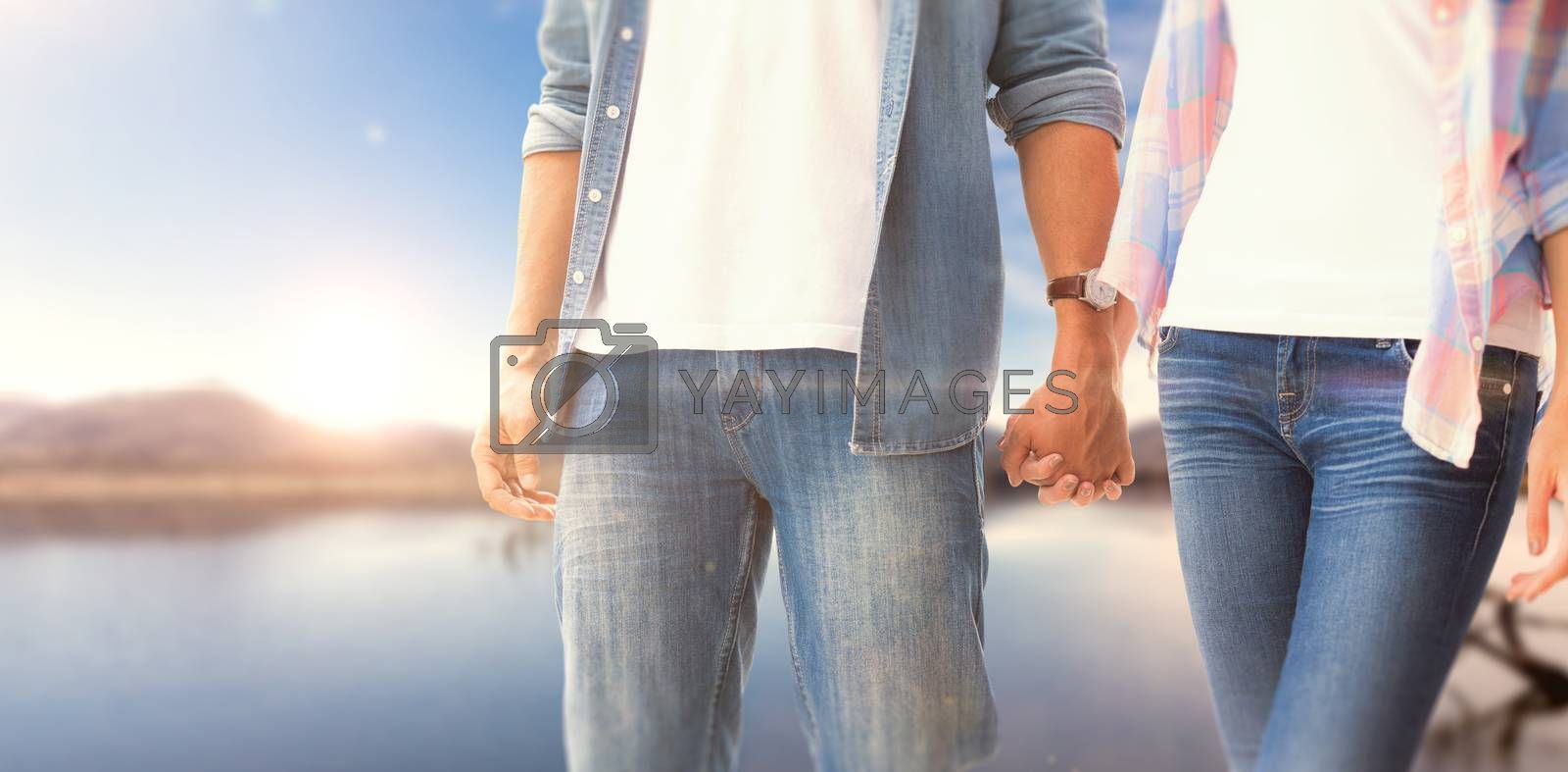 Hip young couple holding hands against lake