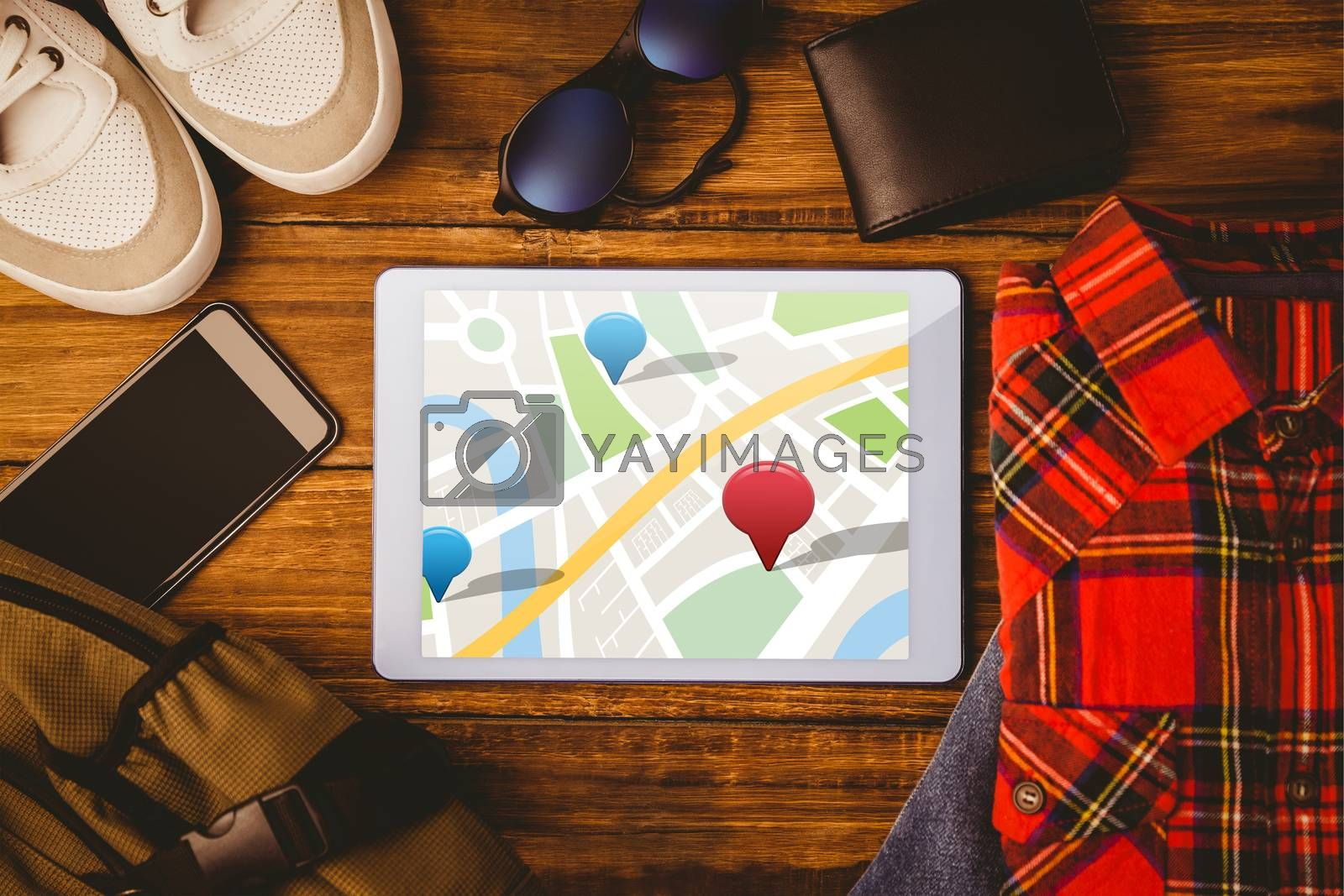 Digitally generated image of navigation pointers  against tablet shirt jean shoes smartphone wallet and bag