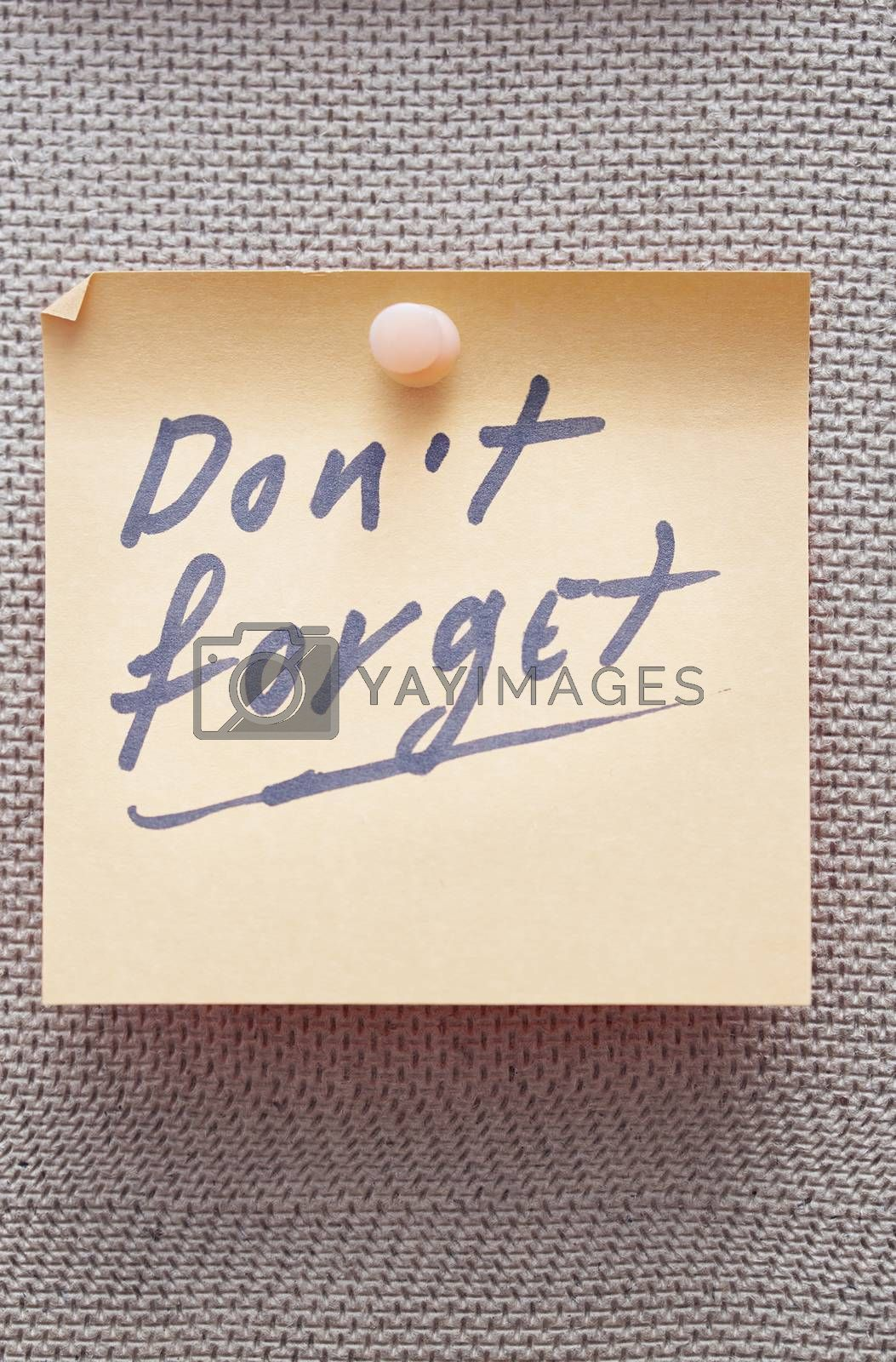 Adhesive note with Do not forget text on a bulletin board
