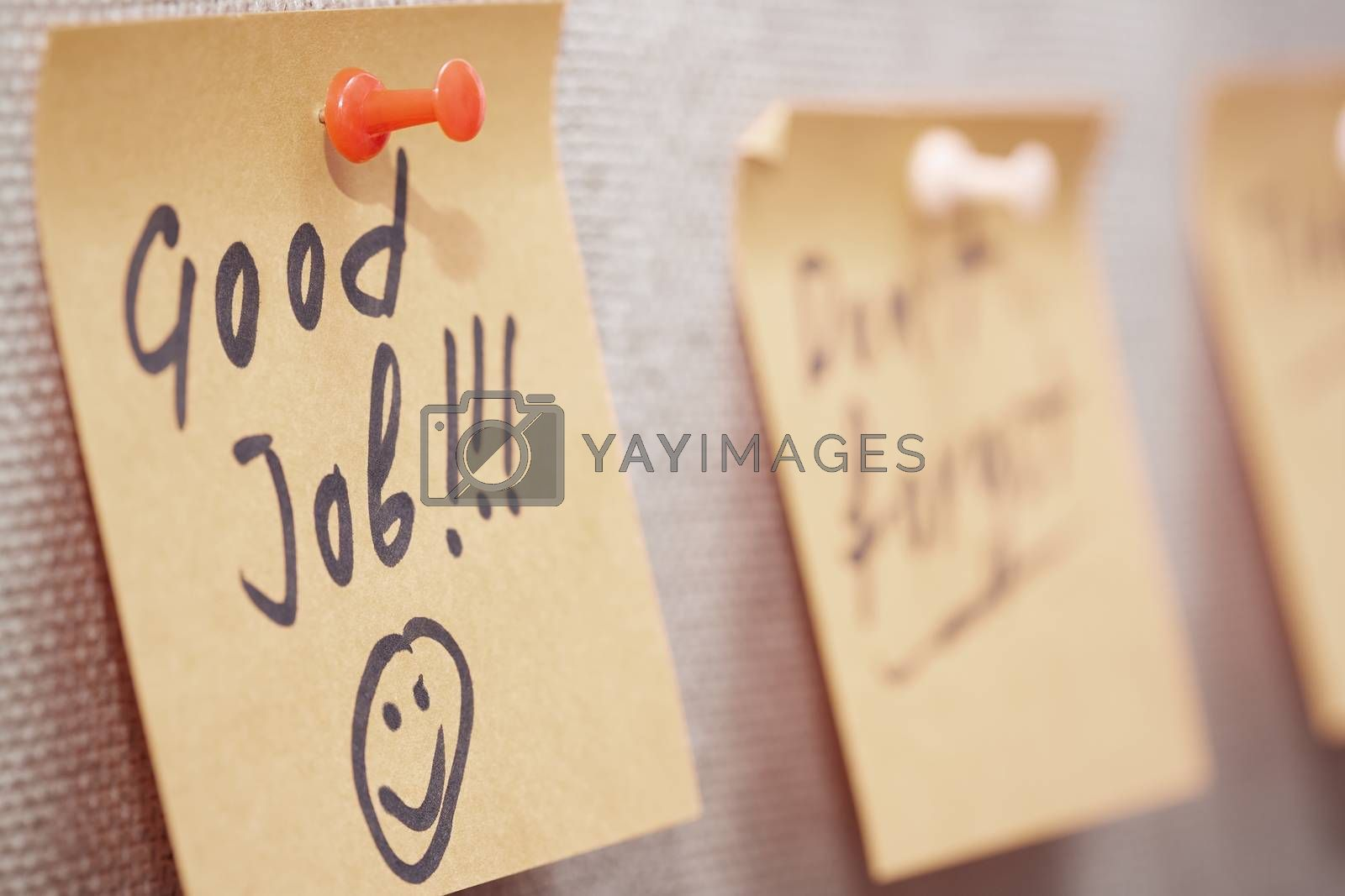 Adhesive note with Good Job text on a cork bulletin board