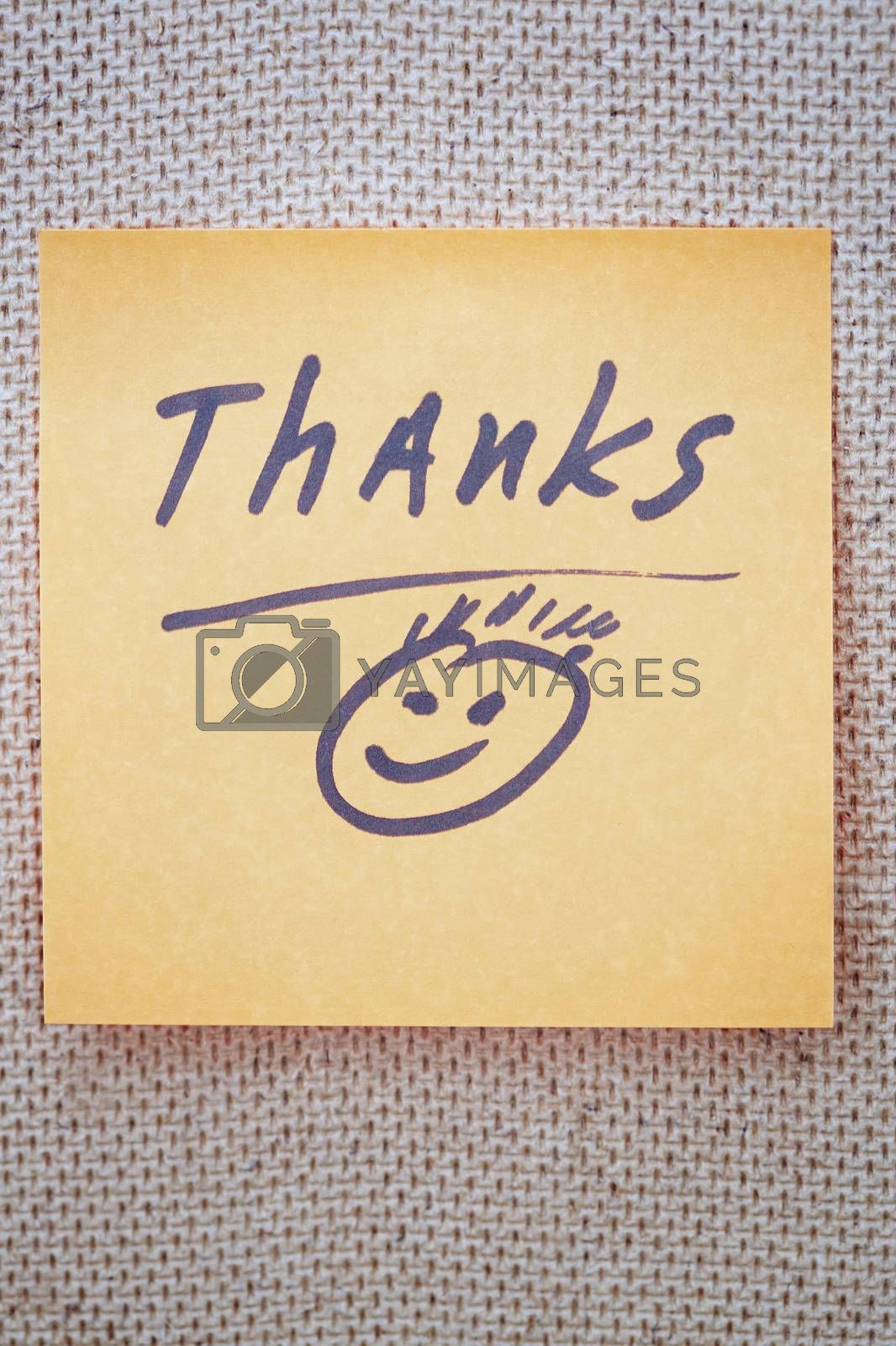 Adhesive note with Thanks text on a bulletin board