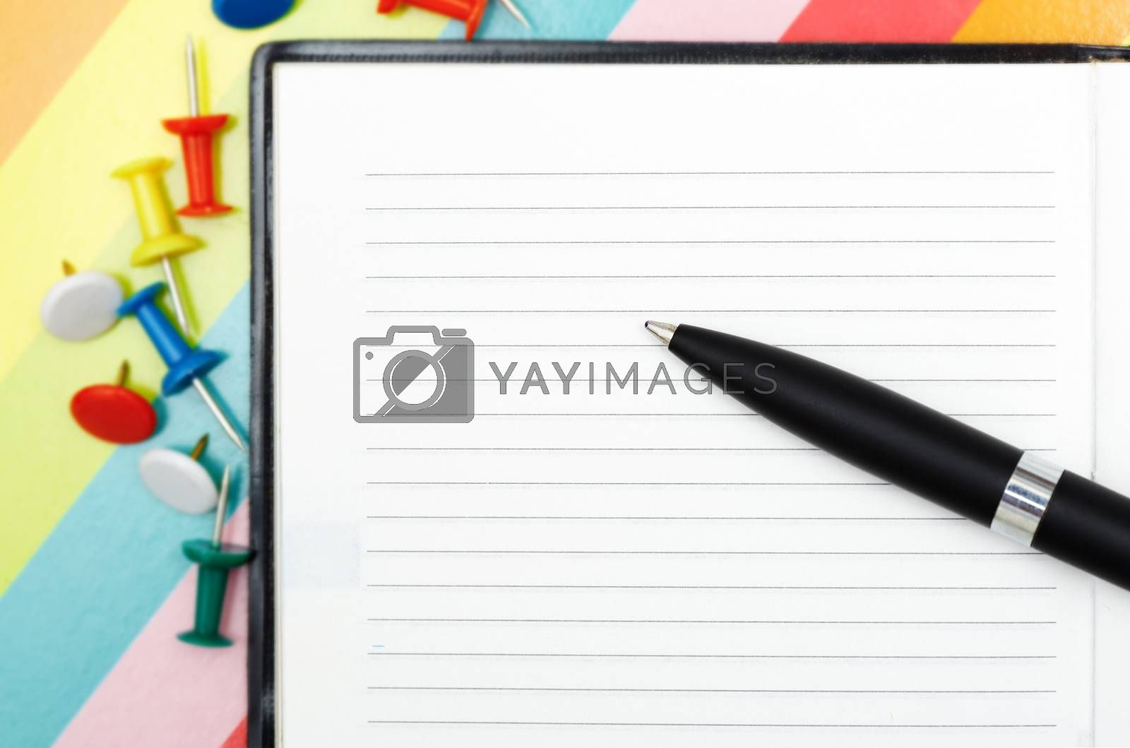 Notepad with pen and pushpins. Close-up photo