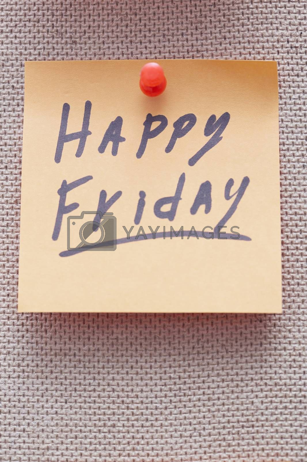 Adhesive note with Happy Friday text on a cork bulletin board