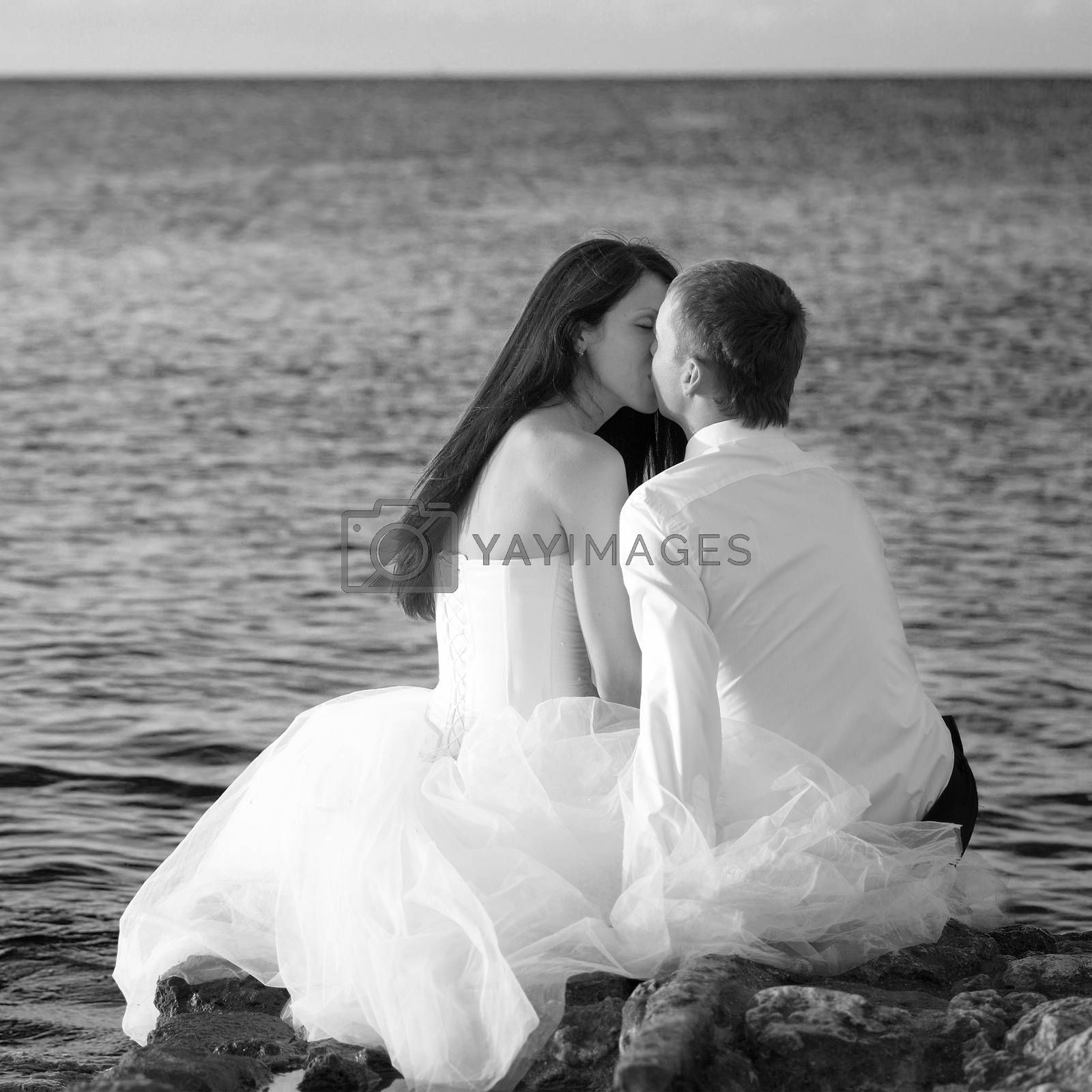 Beautiful wedding couple- bride and groom kissing at the beach. Just married. Black and white