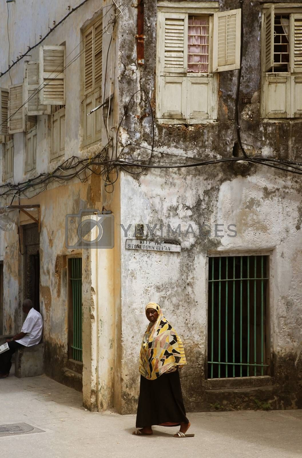 Stone Town, Tanzania - December 30, 2015: Woman in traditional Muslim clothes walking on the street of Stone Town. Background is another house.