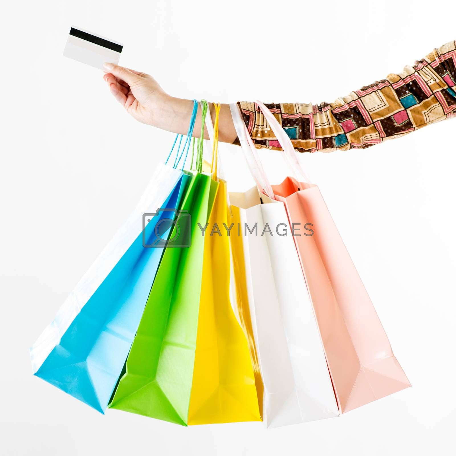 Close up of a woman hand with many shopping bags and credit card. White background.
