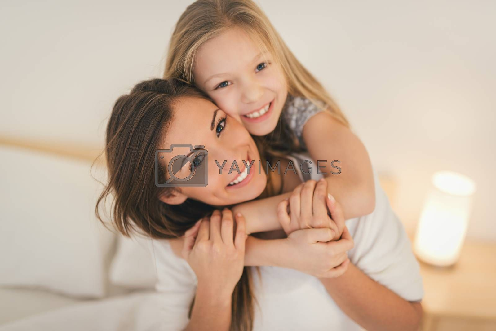 Beautiful smiling mother and her daughter hugging in bed. They are sitting on bed at pajamas and smiling looking at camera.