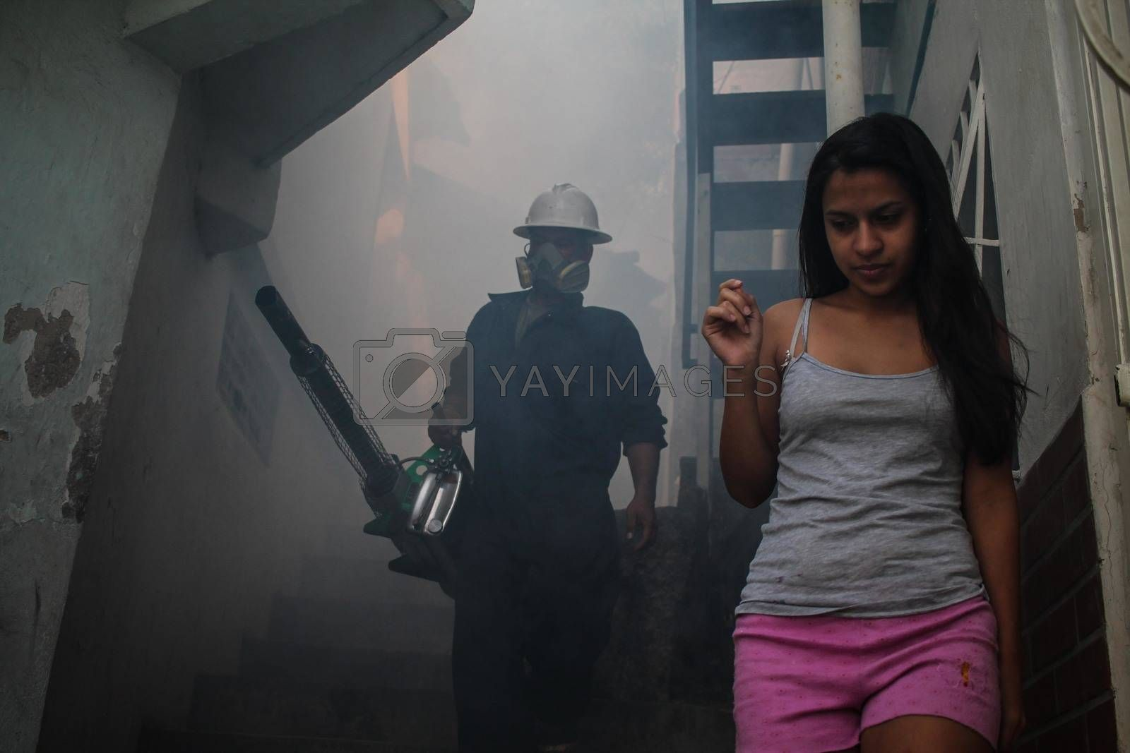 VENEZUELA, Caracas: A member of a fumigation crew waits for a girl to exit her home to allow for the extermination of Aedes mosquitoes carrying the Zika virus in the slums of Caracas, Venezuela on February 3, 2016. As of February 4, there have been reports of at least 255 cases of the rare Guillain-Barre syndrome — which causes the immune system to attack the nerves — potentially linked to the Zika virus in Venezuela.