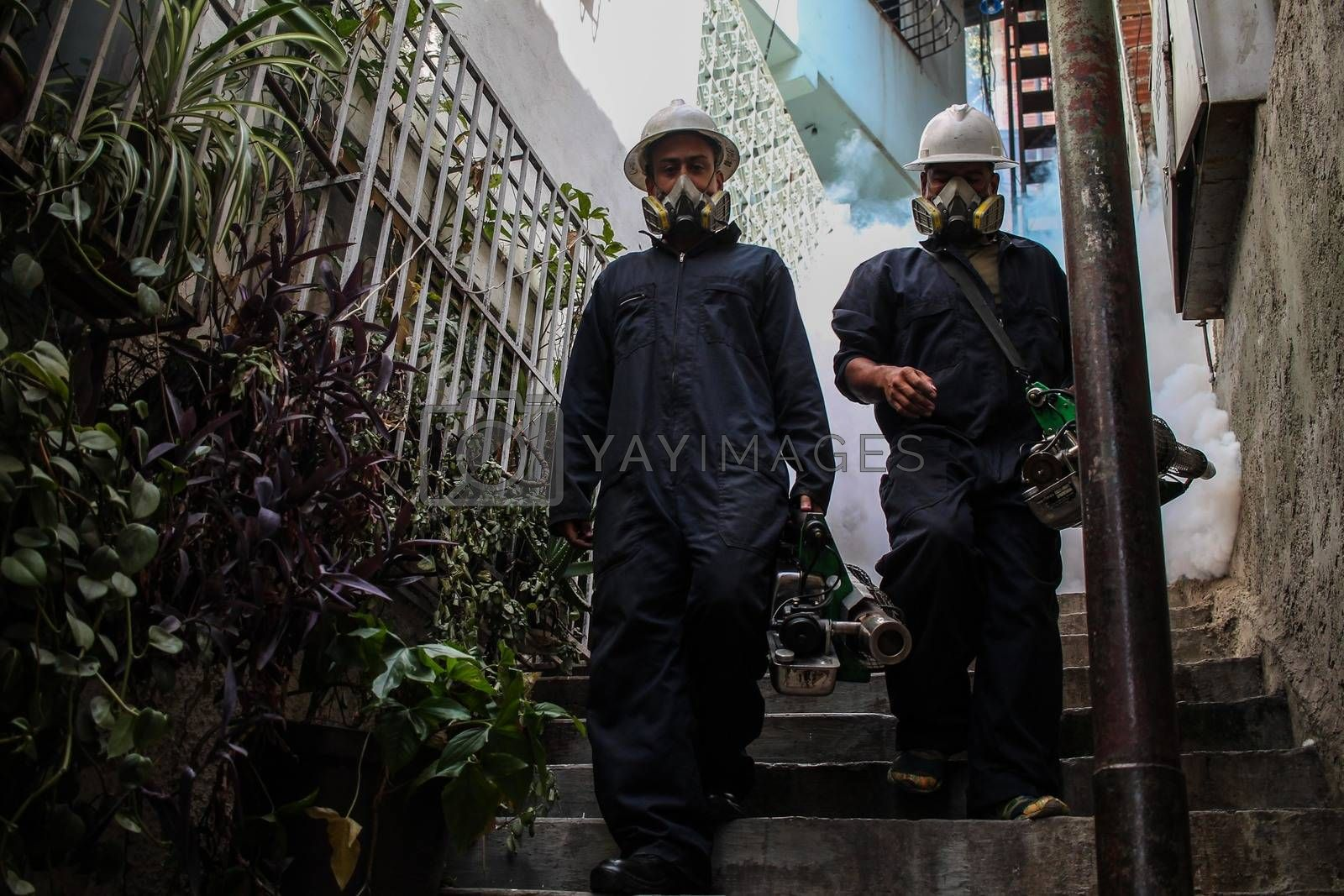 VENEZUELA, Caracas: Members of a fumigation crew exit a home after exterminating mosquitoes carrying the rapidly spreading Zika virus in the slums of Caracas, Venezuela on February 3, 2016. As of February 4, there have been reports of at least 255 cases of the rare Guillain-Barre syndrome — which causes the immune system to attack the nerves — potentially linked to the Zika virus in Venezuela.