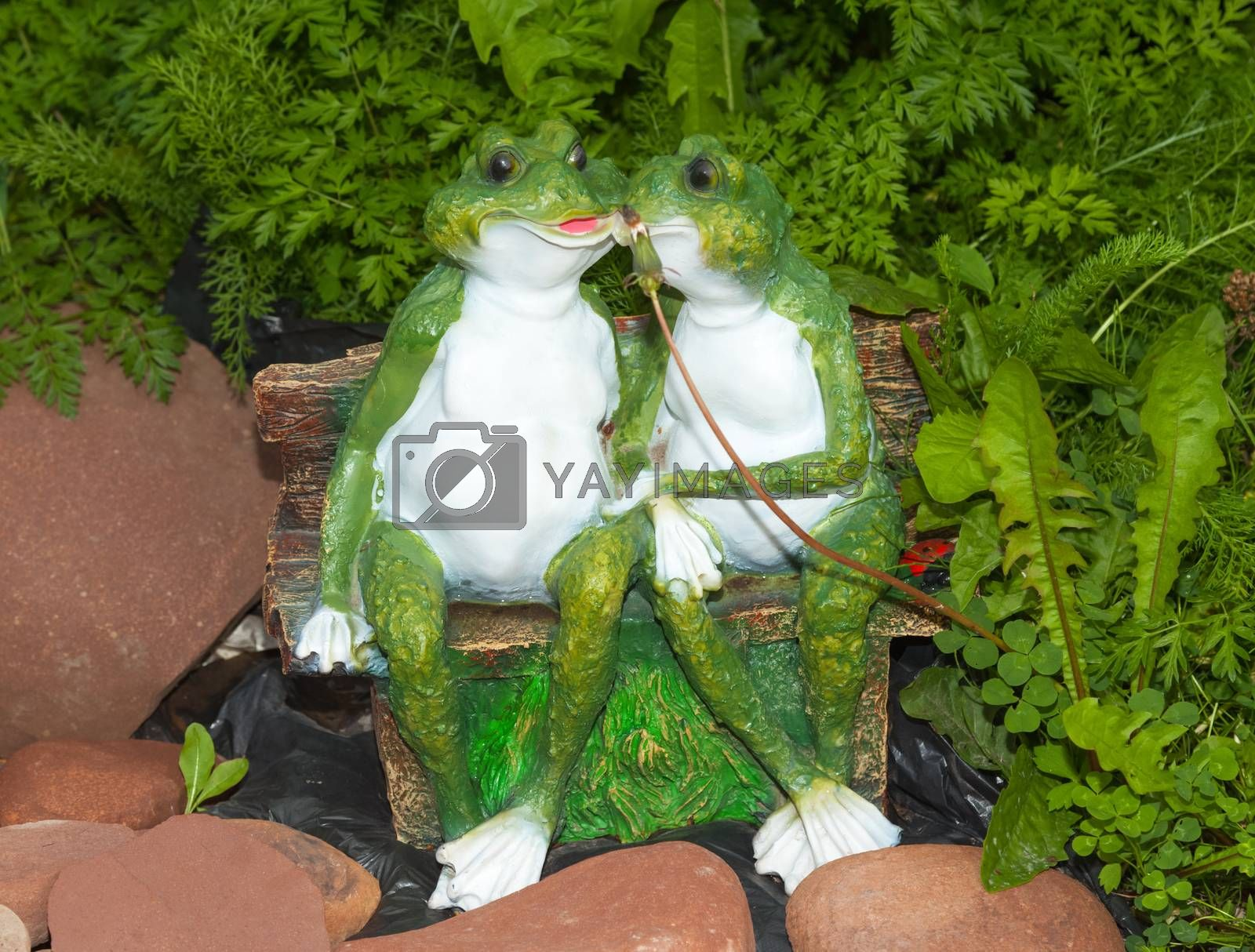 Two green ornament frog sitting on a bench near a stones in the tall grass