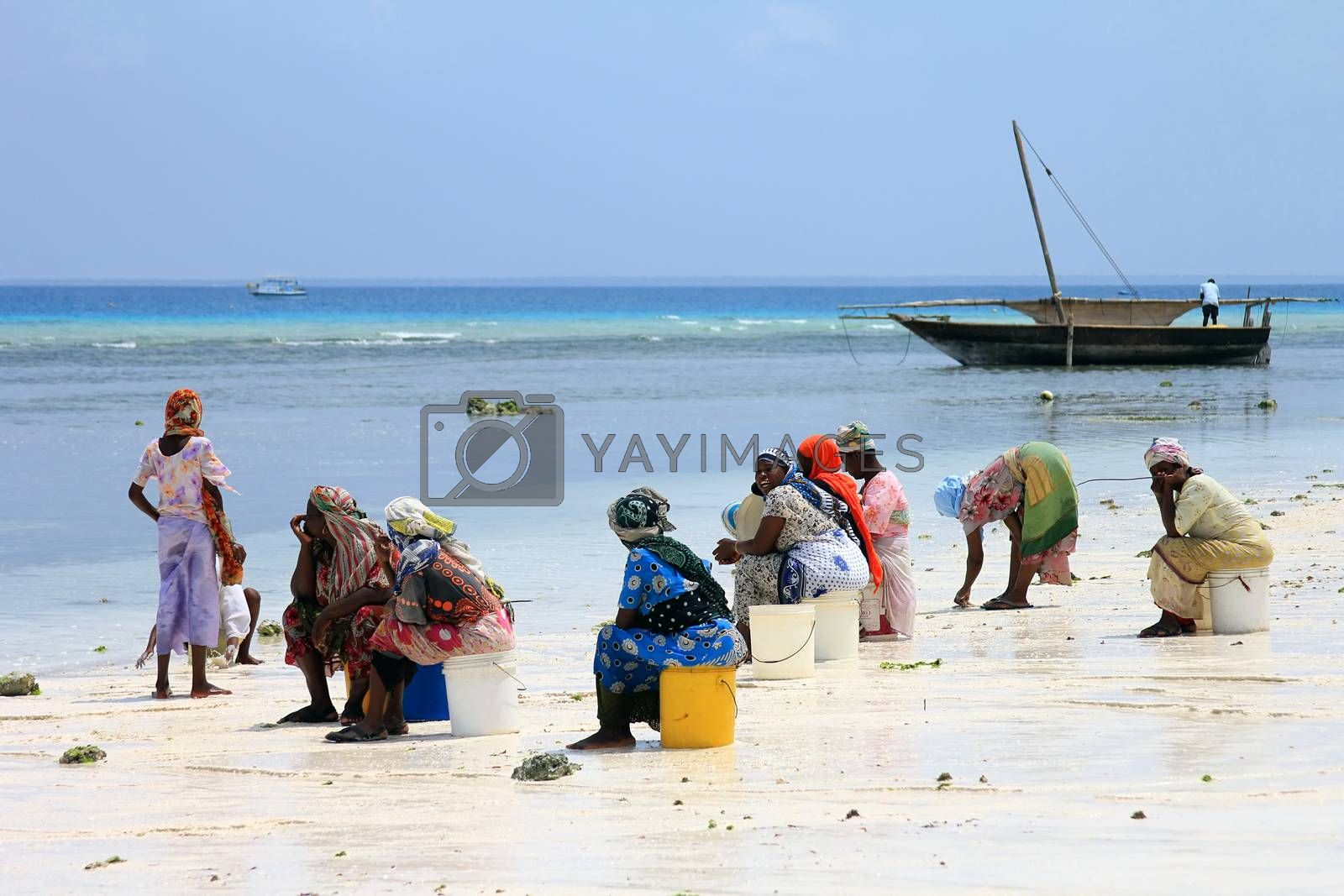Nungwi, Zanzibar, Tanzania - January 11, 2016:  African women in traditional dress on the beach of village Nungwi. Zanzibar, Tanzania